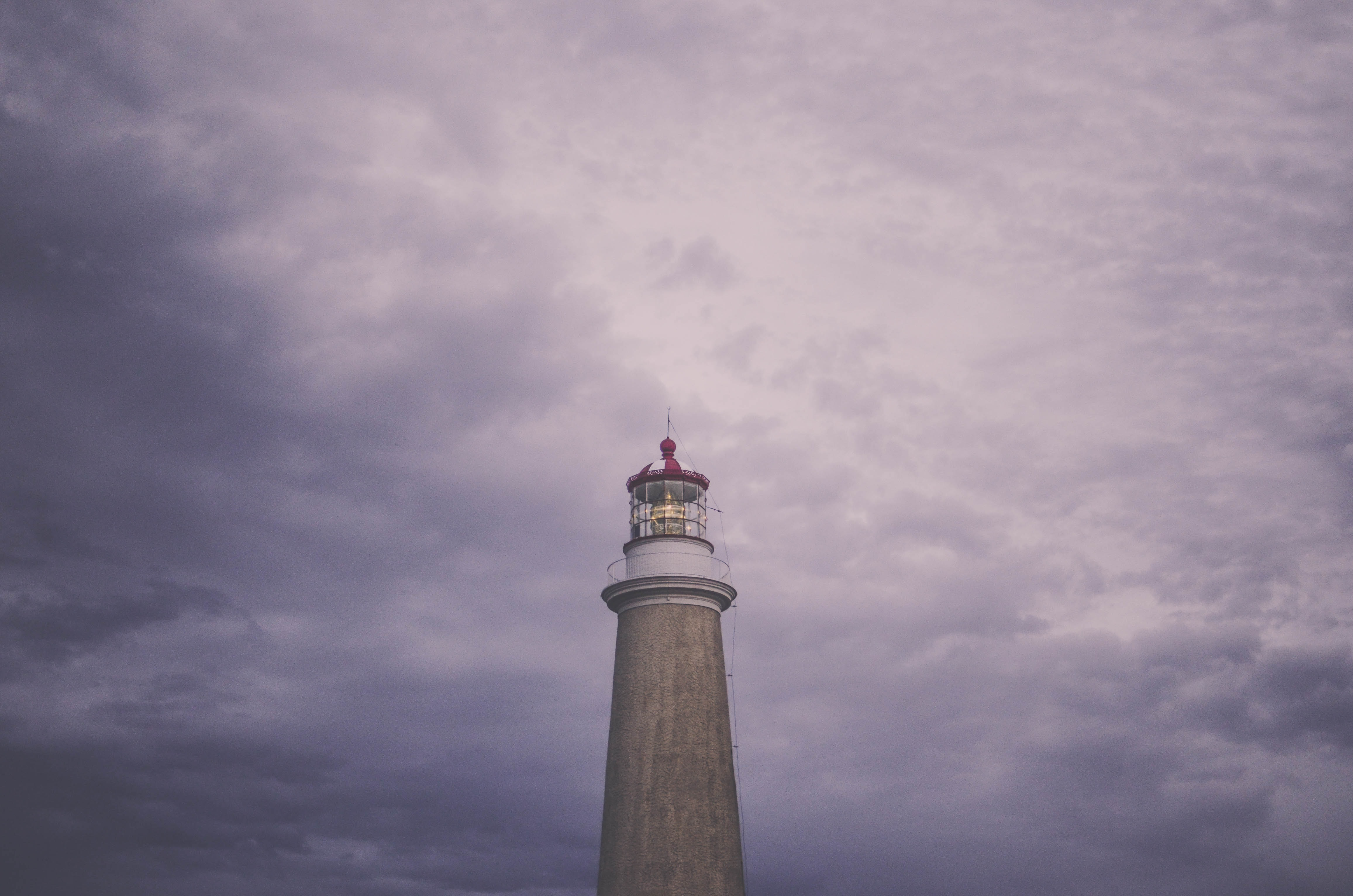 brown lighthouse under cloudy daytime