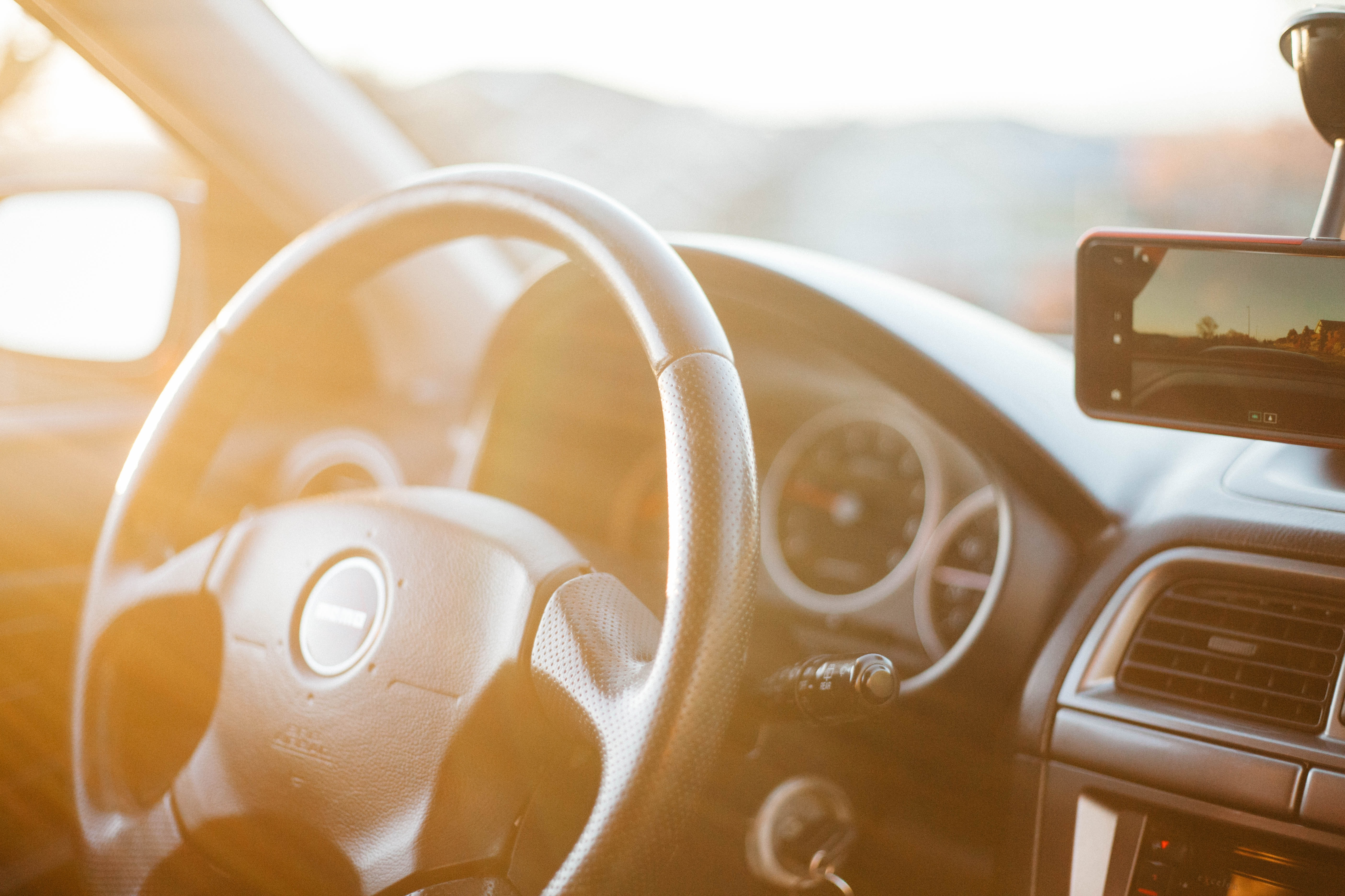 Sunlit steering wheel and dashboard of the car with the mobile phone attached to the windscreen in Bellingham