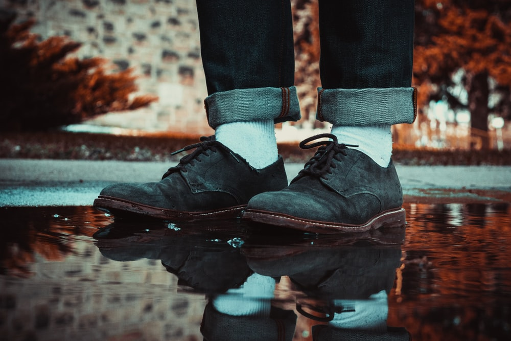 person wearing brown leather shoes stepping on water puddle
