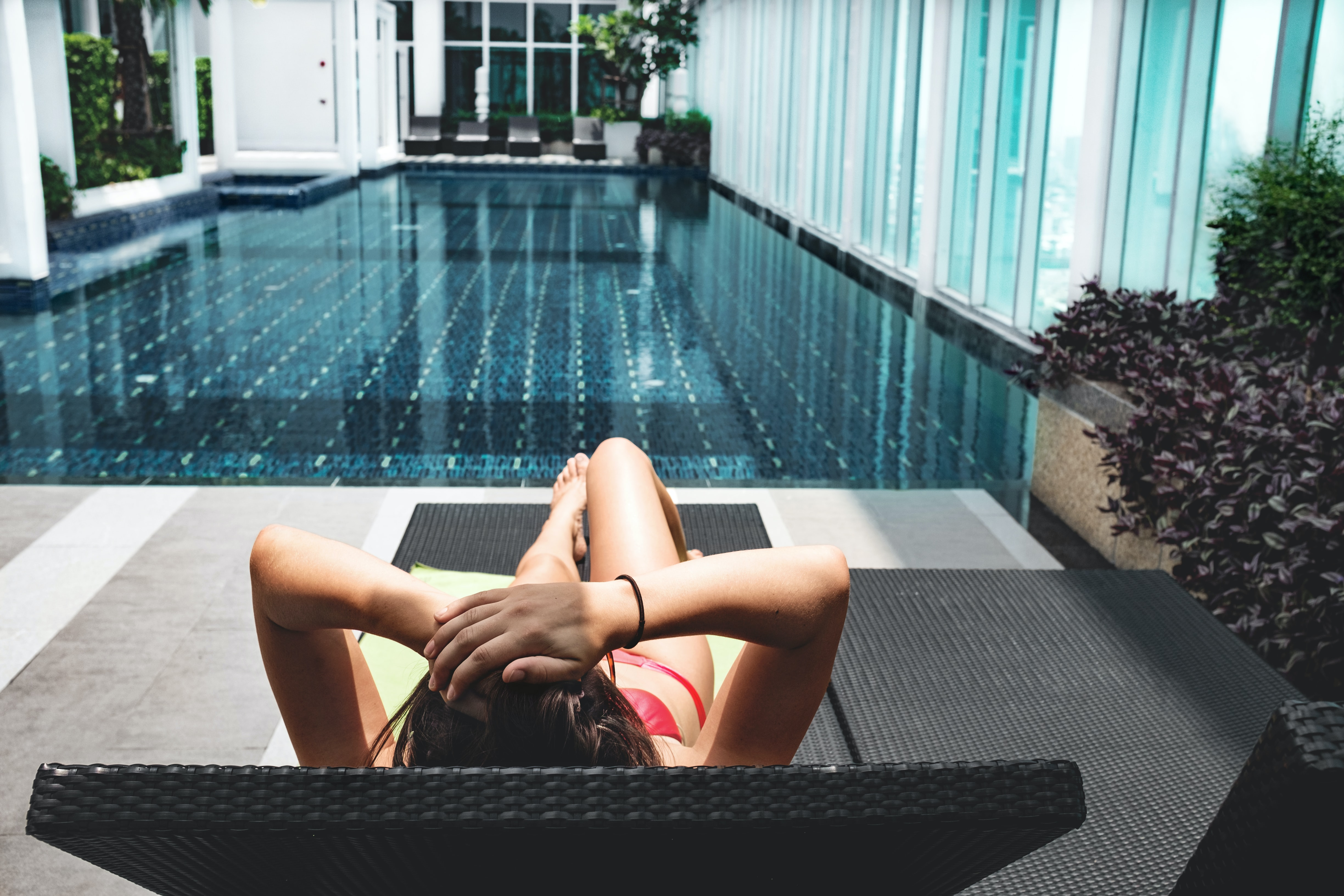 A woman in a bikini lays on a lounge chair facing a pool