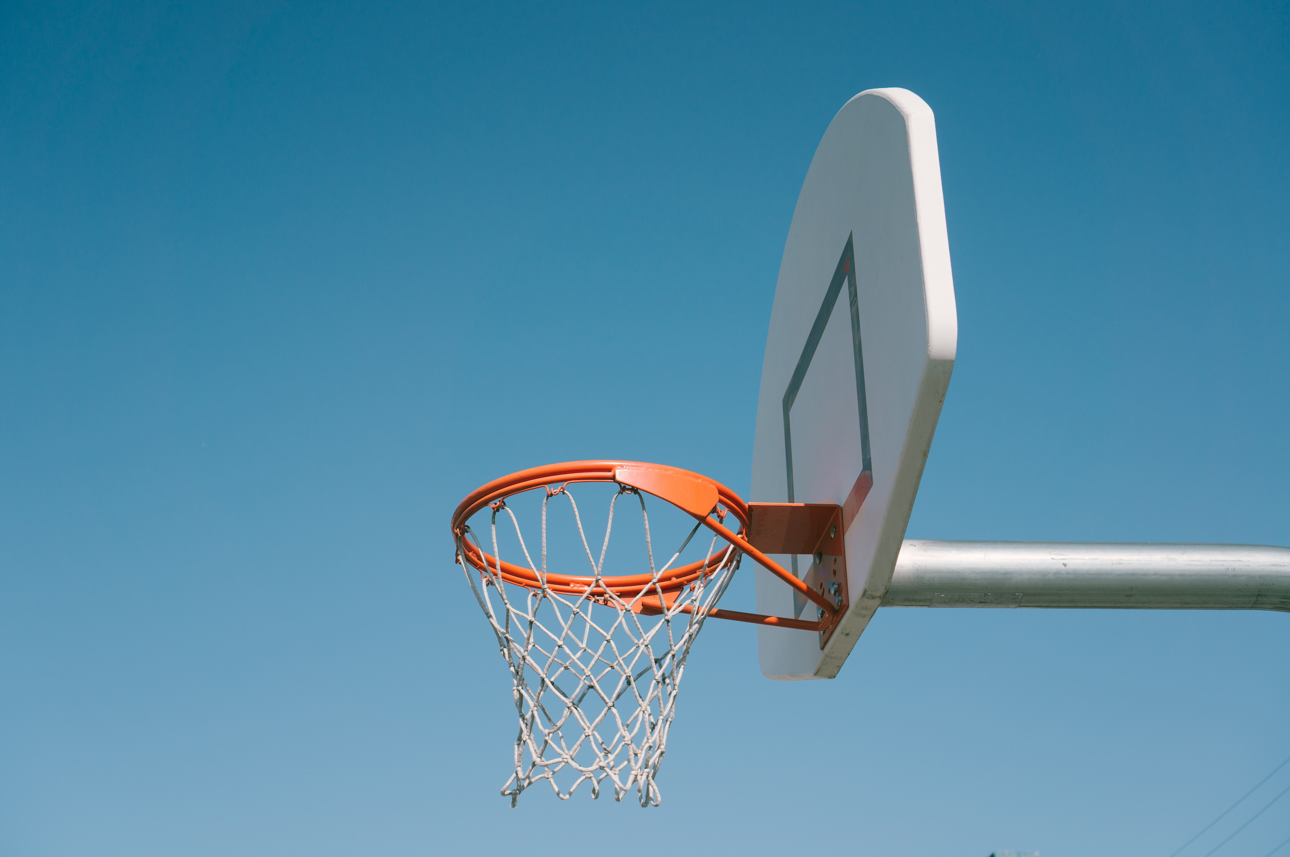 A basic photo of an outdoor basketball net, rim and backboard
