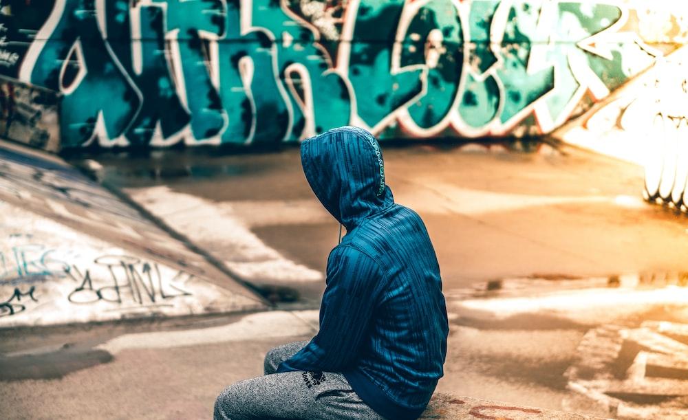 person sitting near graffiti artwork