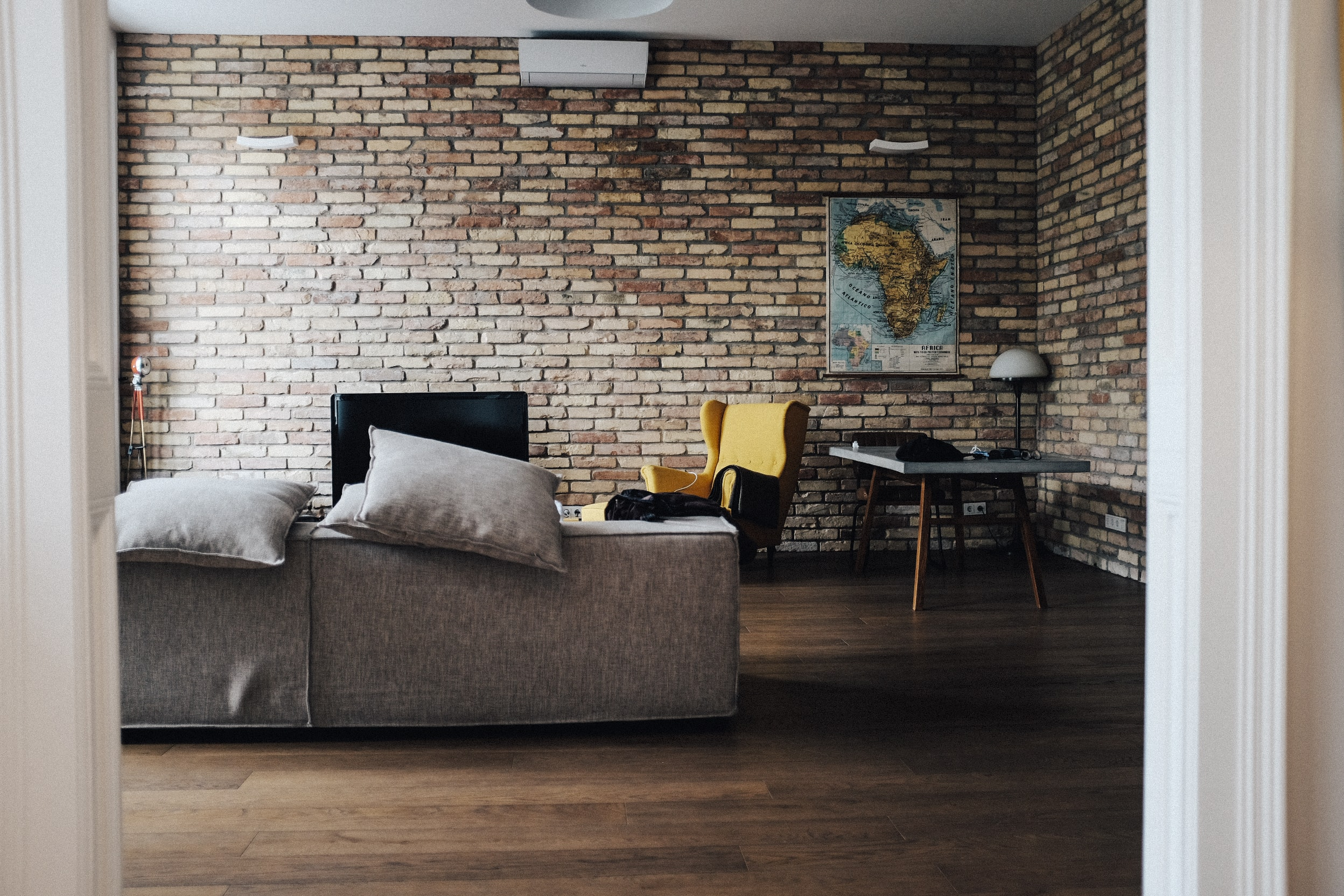 A living room with a sofa, a television, an armchair and a map on the brick wall