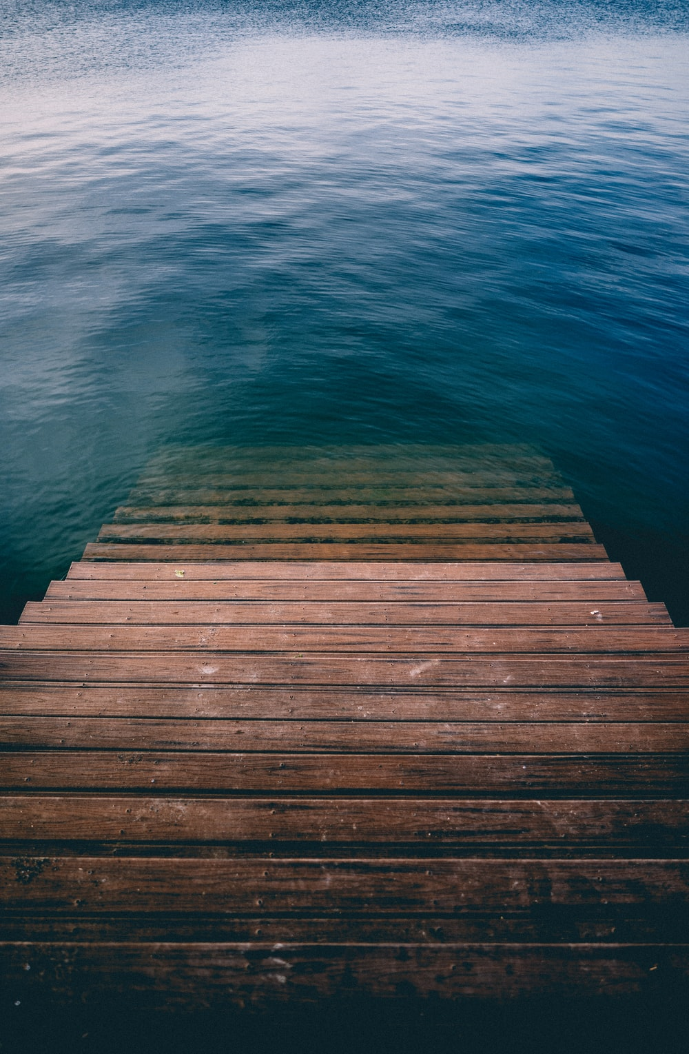 brown wooden stair on calm body of water