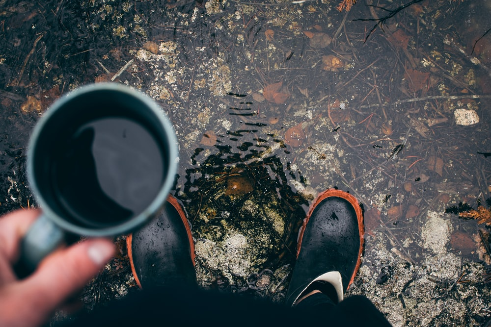 person holding coffee mug with pair of black shoes during daytime