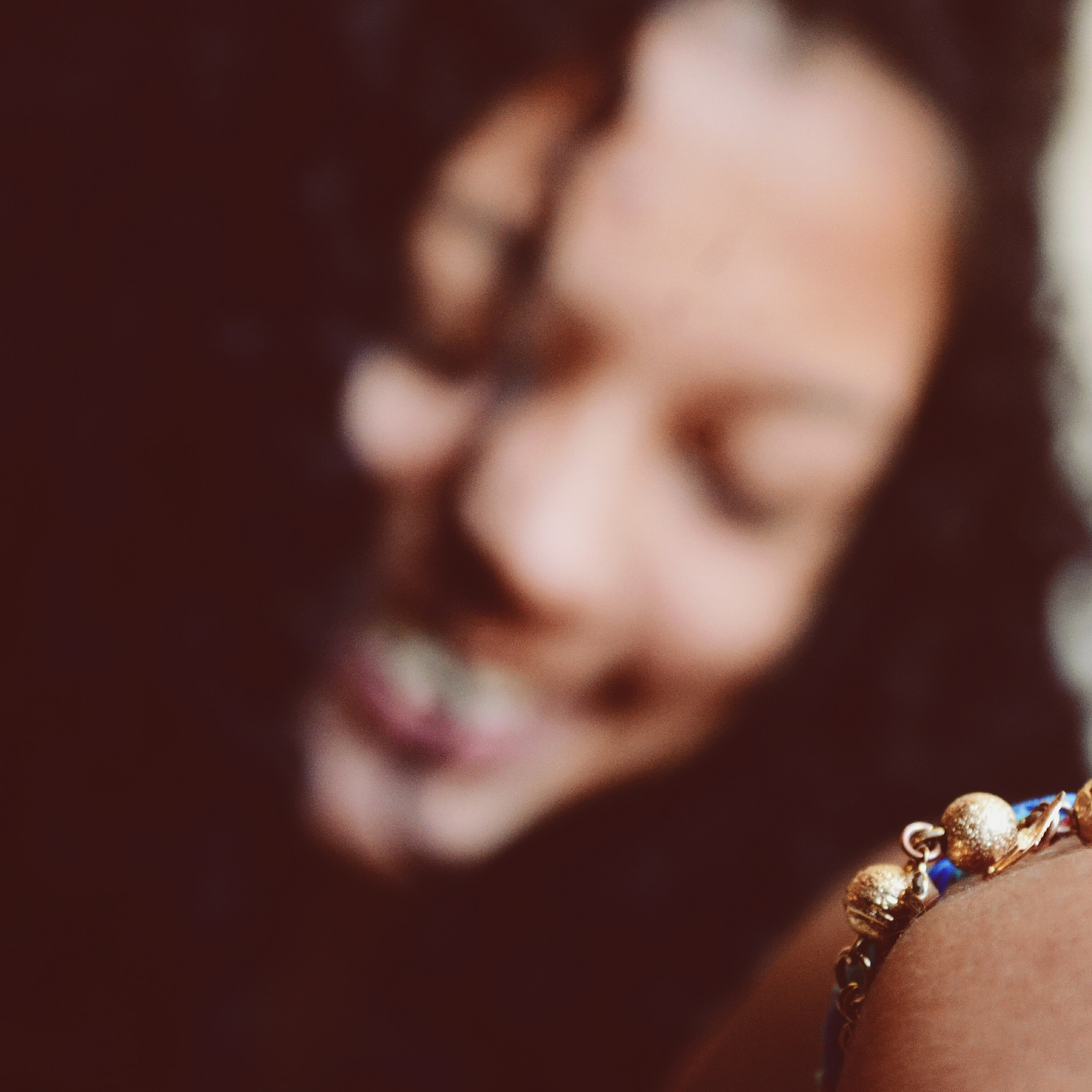 A smiling woman with a blurred face holding forward a bracelet on her wrist