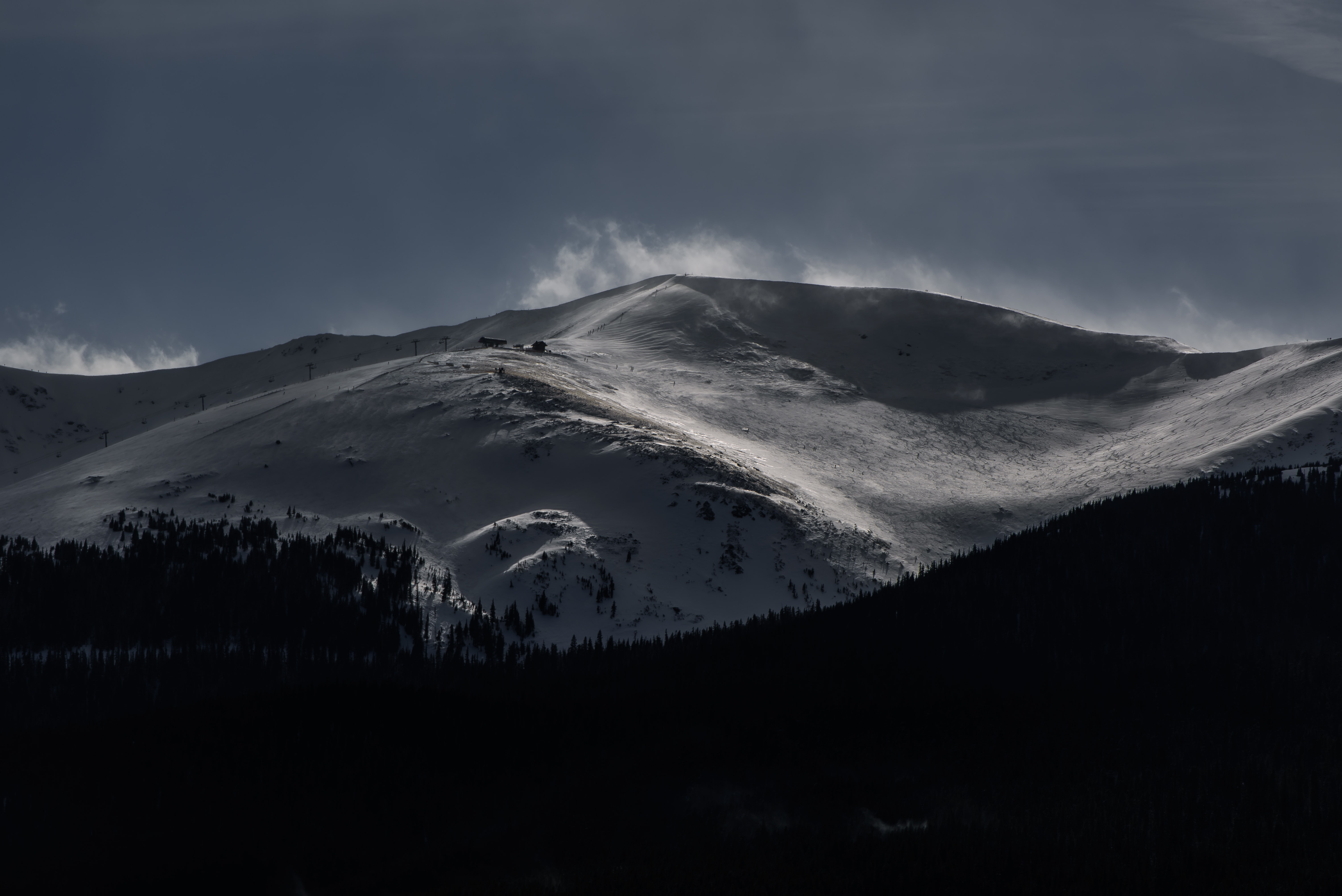 A snow-covered mountain slope with a ski lift in the evening