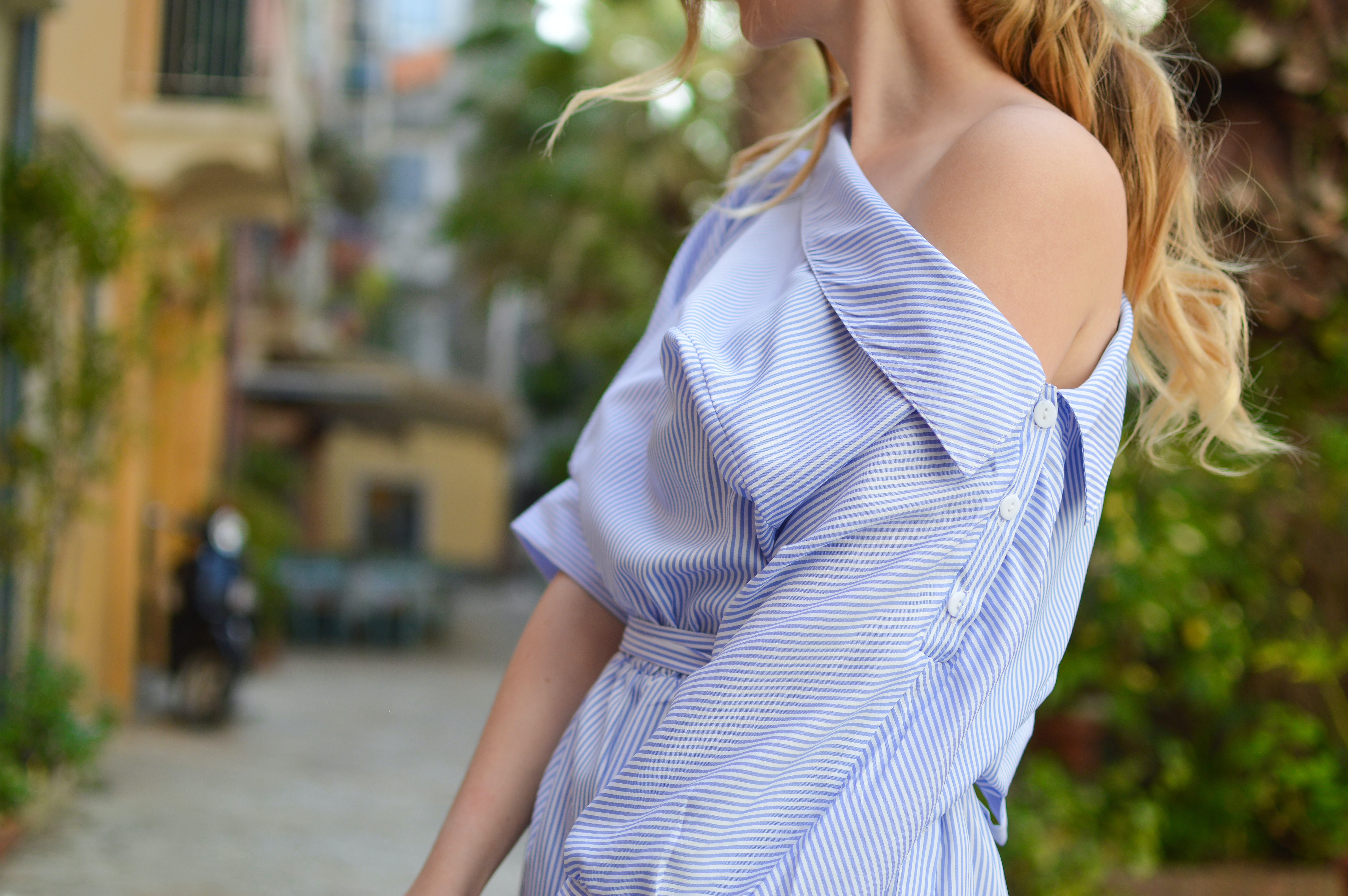 Woman wearing a blue and white striped off the shoulder blouse