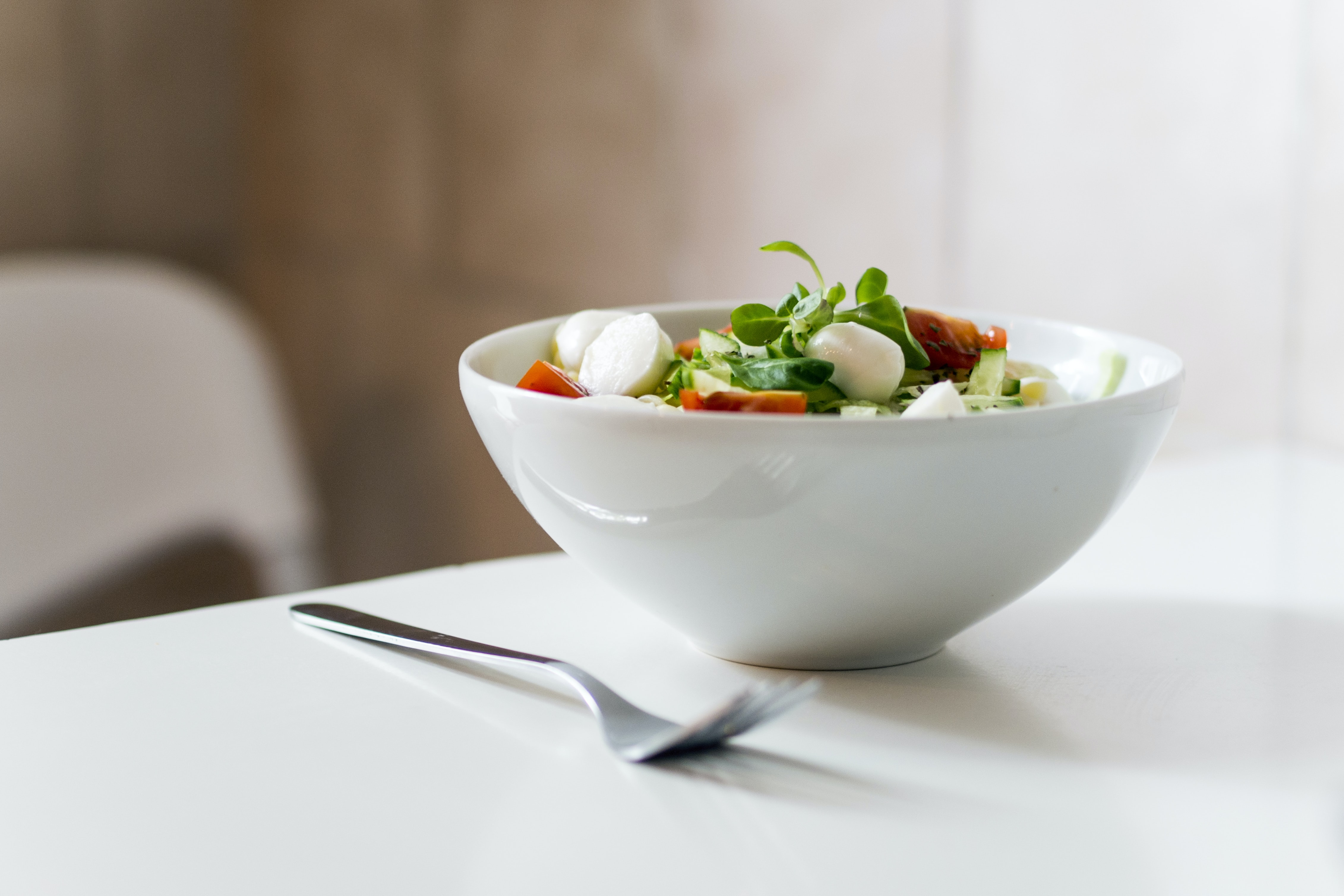 bowl of vegetable beside fork place on table