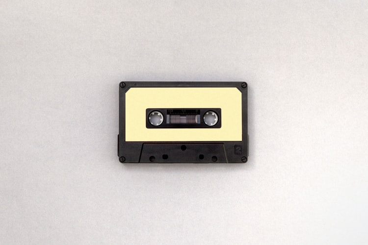A photo of a casette tape on a plain background. The tape is black with a blank yellow sticker on it.