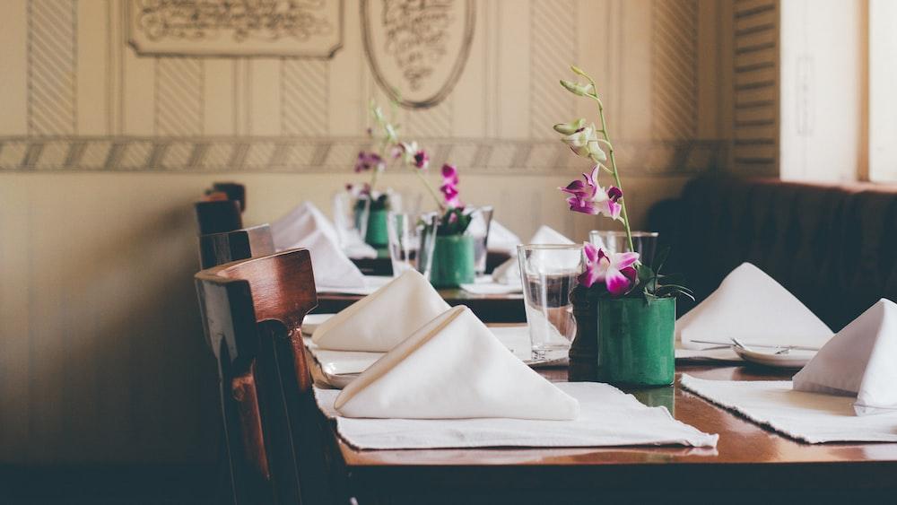 purple petaled flower on table with table napkins