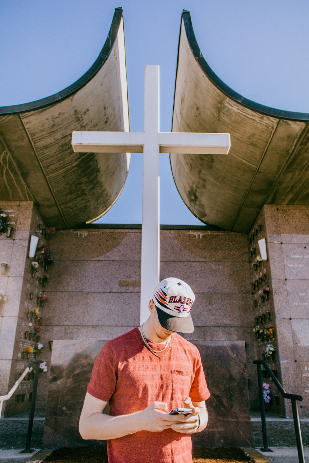 man holding smartphone and standing near cross statue
