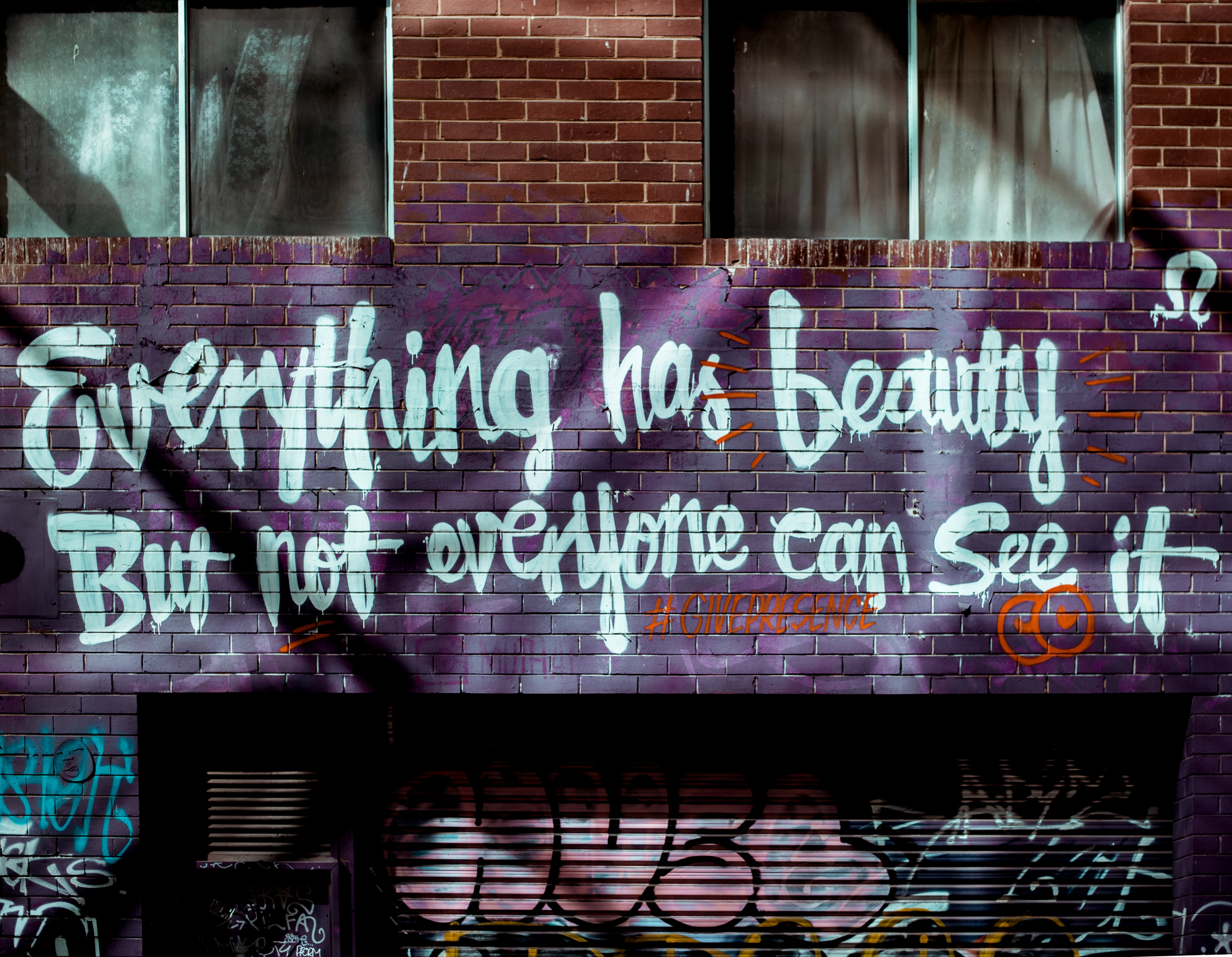 "Brick wall art in Melbourne reads ""Everything has beauty but not everyone can see it"""
