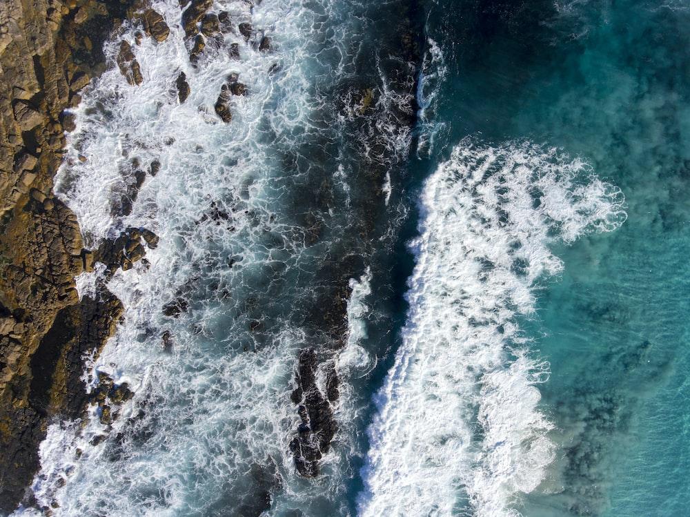 bird's eye view of raging water waves against rock