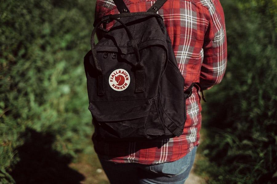 woman wearing a black fjallraven kanken backpack