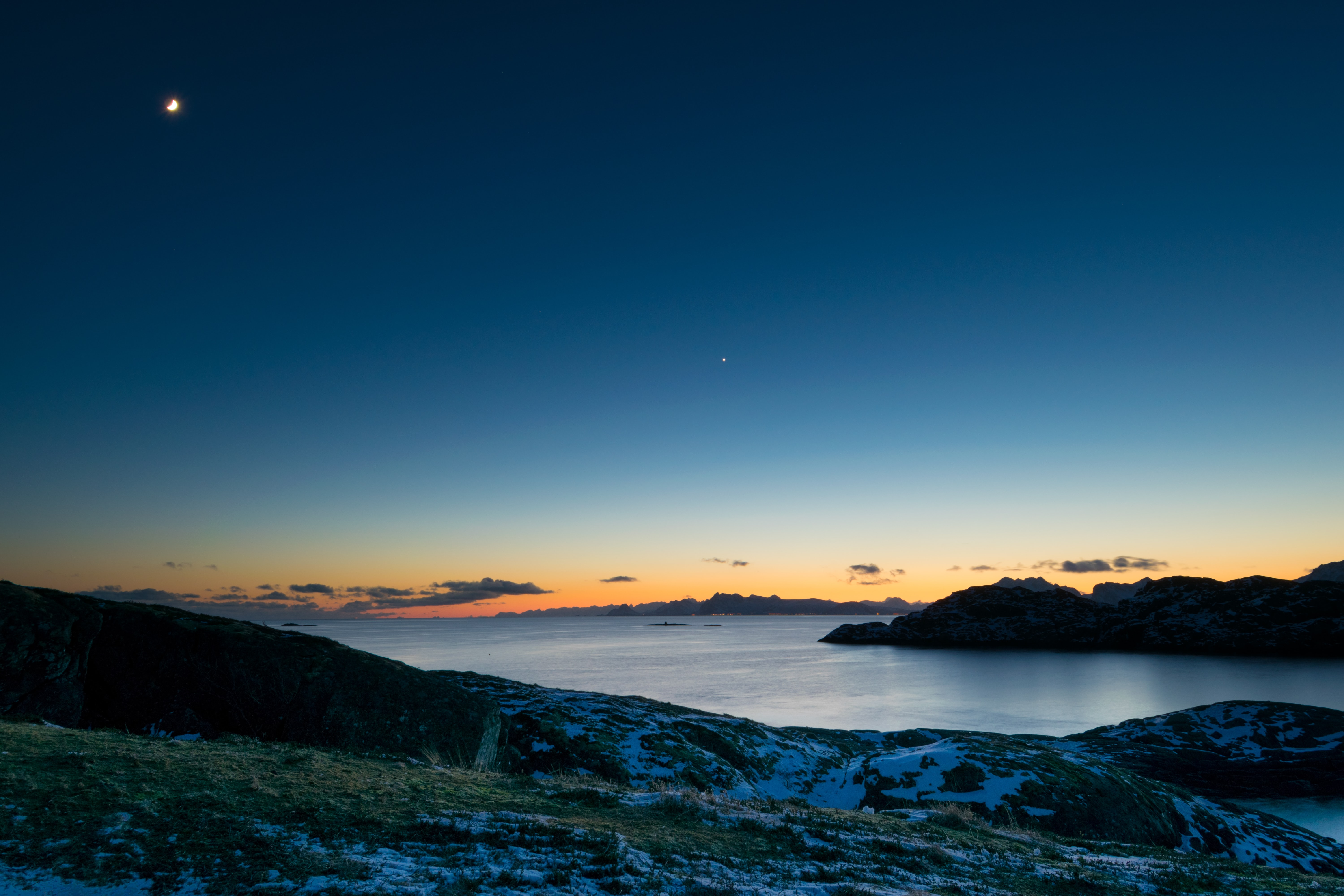 Moon rise during sunset on an inky night sky over Lofoten
