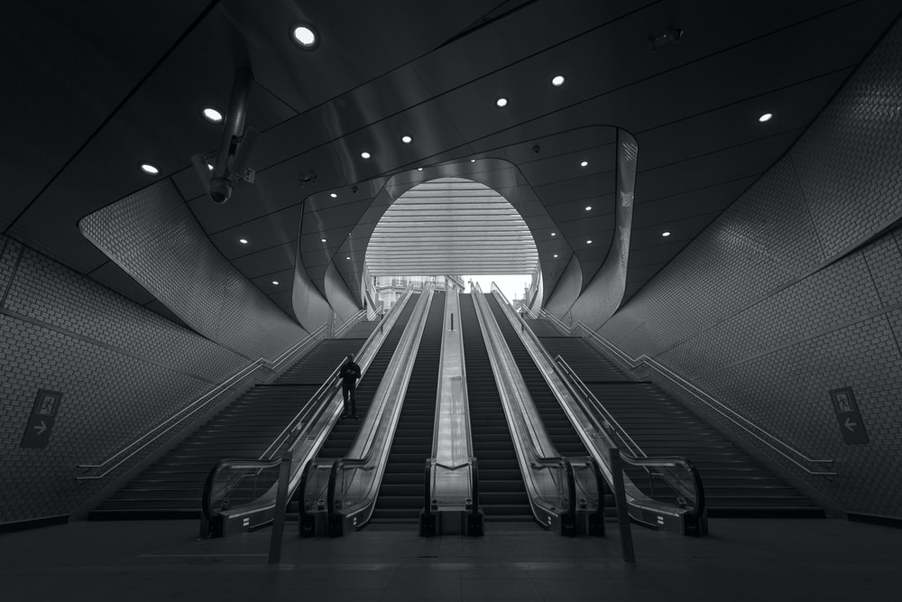 grayscale photography of person on escalator