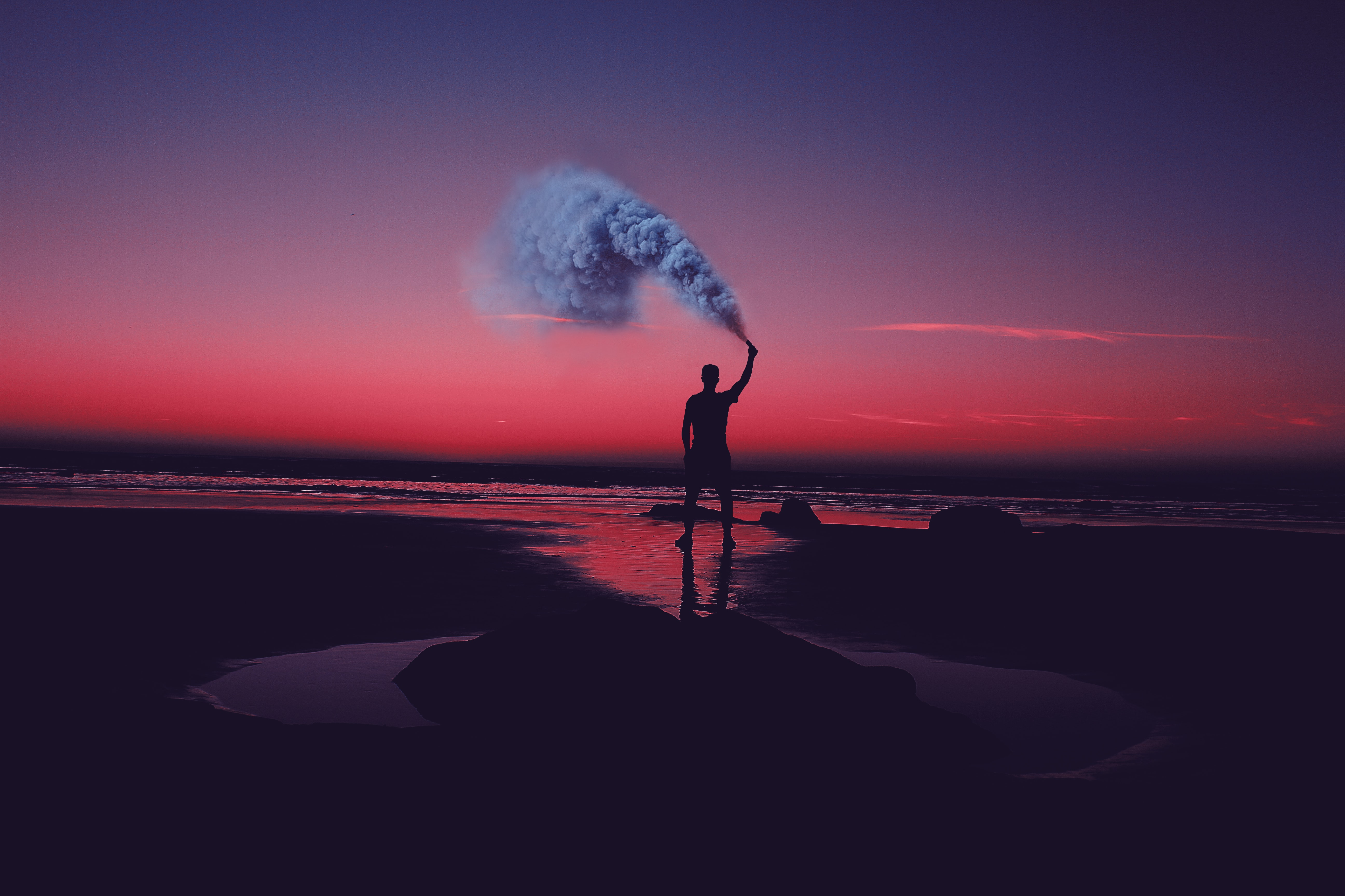 A silhouette of a man holding a smoke bomb on a deserted beach, with a pink sunset sky in the background