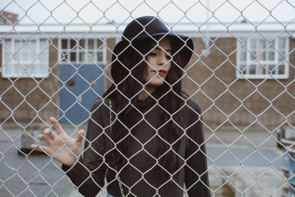 woman touching cyclone fence