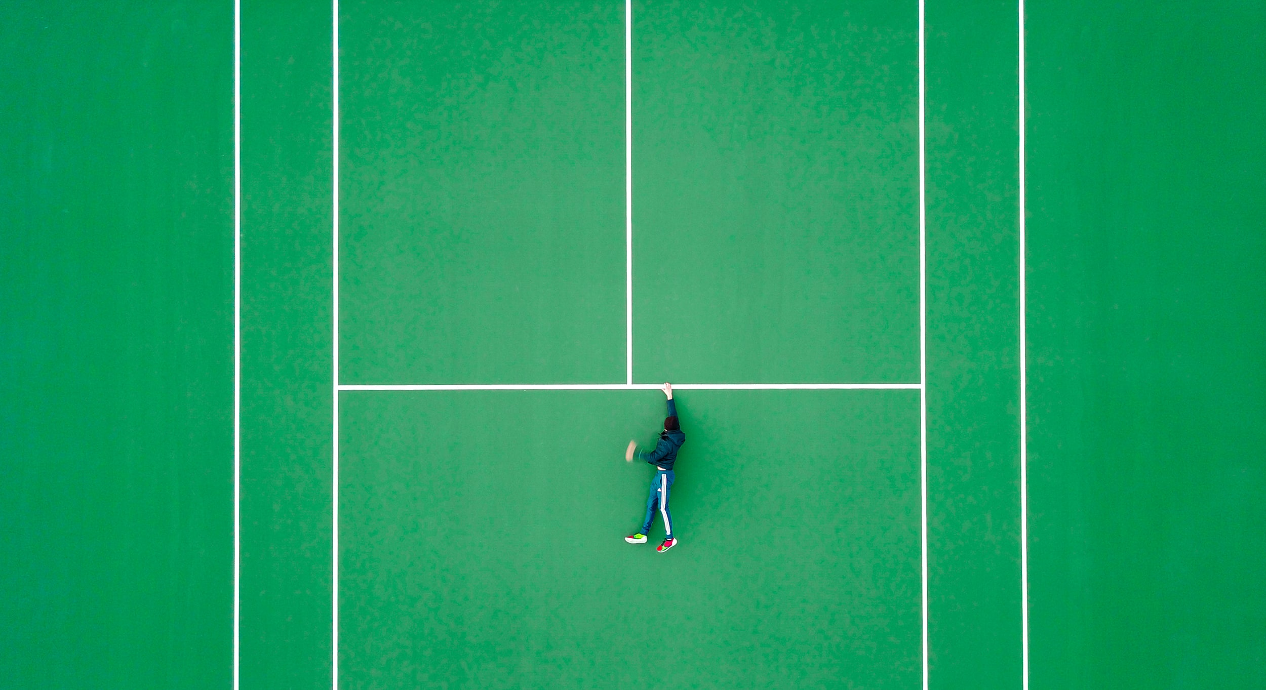 aerial photography of person lying on tennis court