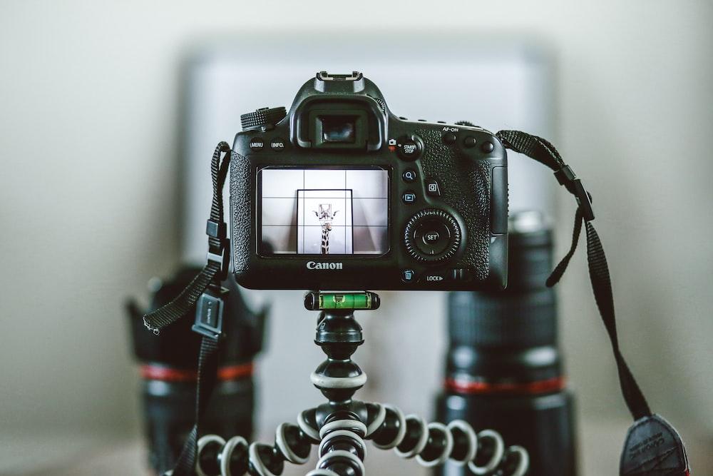 black Canon SLR camera attached on gorillapod