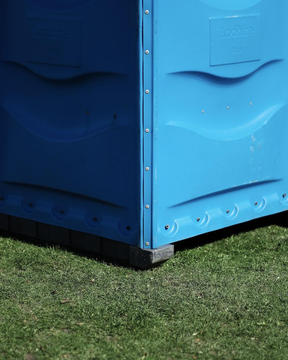 blue metal storage box on green grass