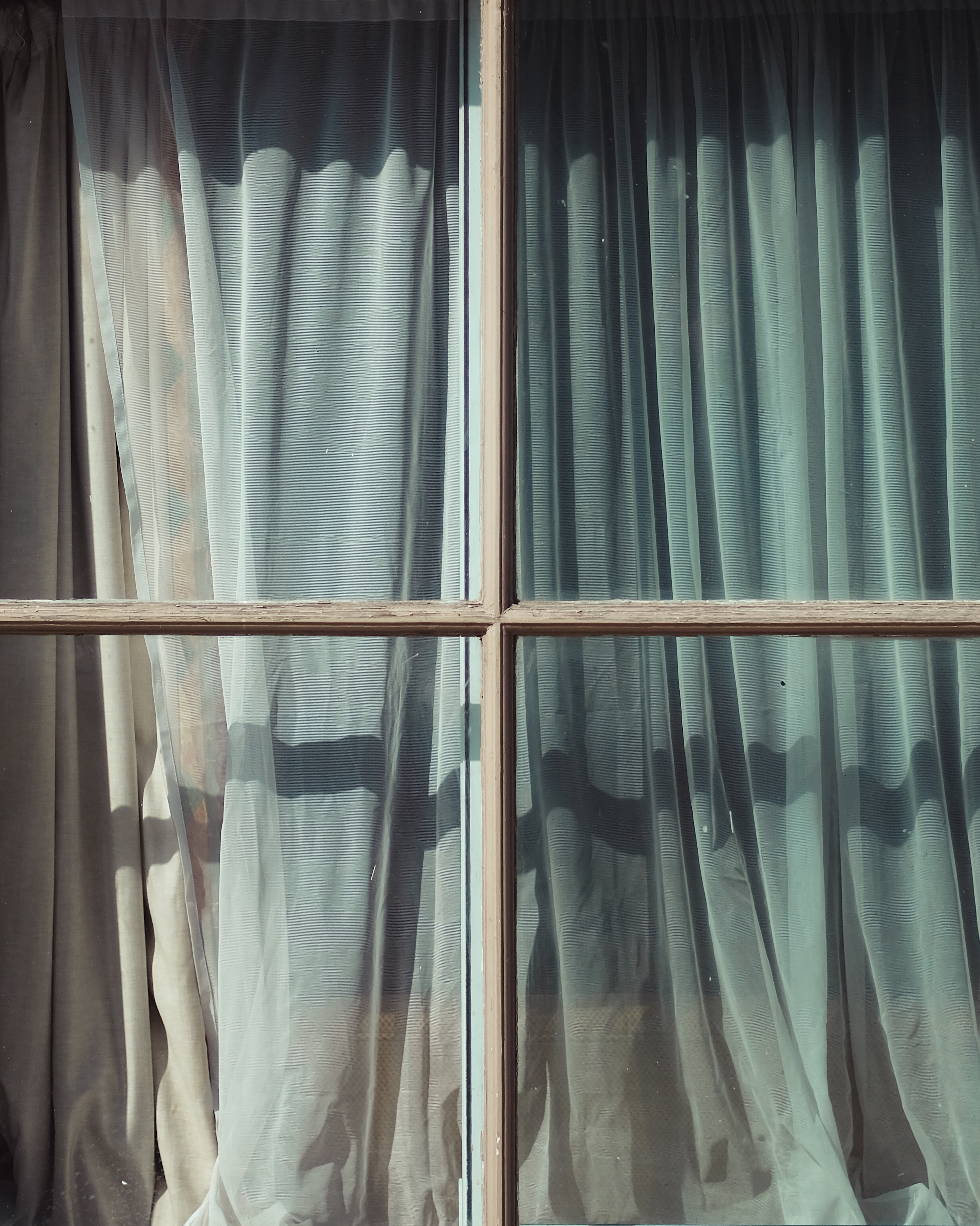 glass window with teal and white curtain