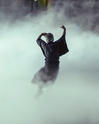 man in black robe surrounded by smoke inside room