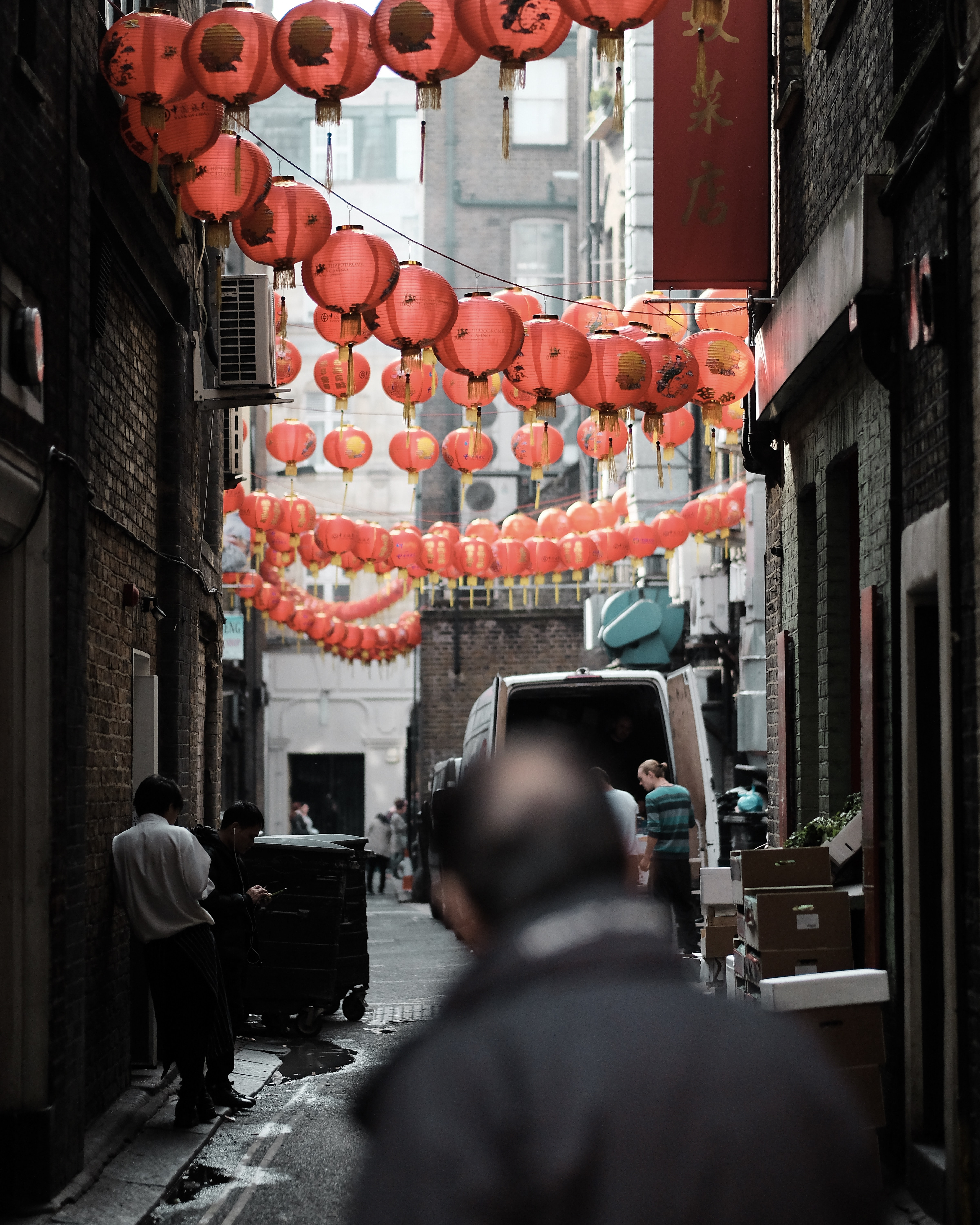 A man looks down an alleyway with strings of paper lanterns hung from the buildings