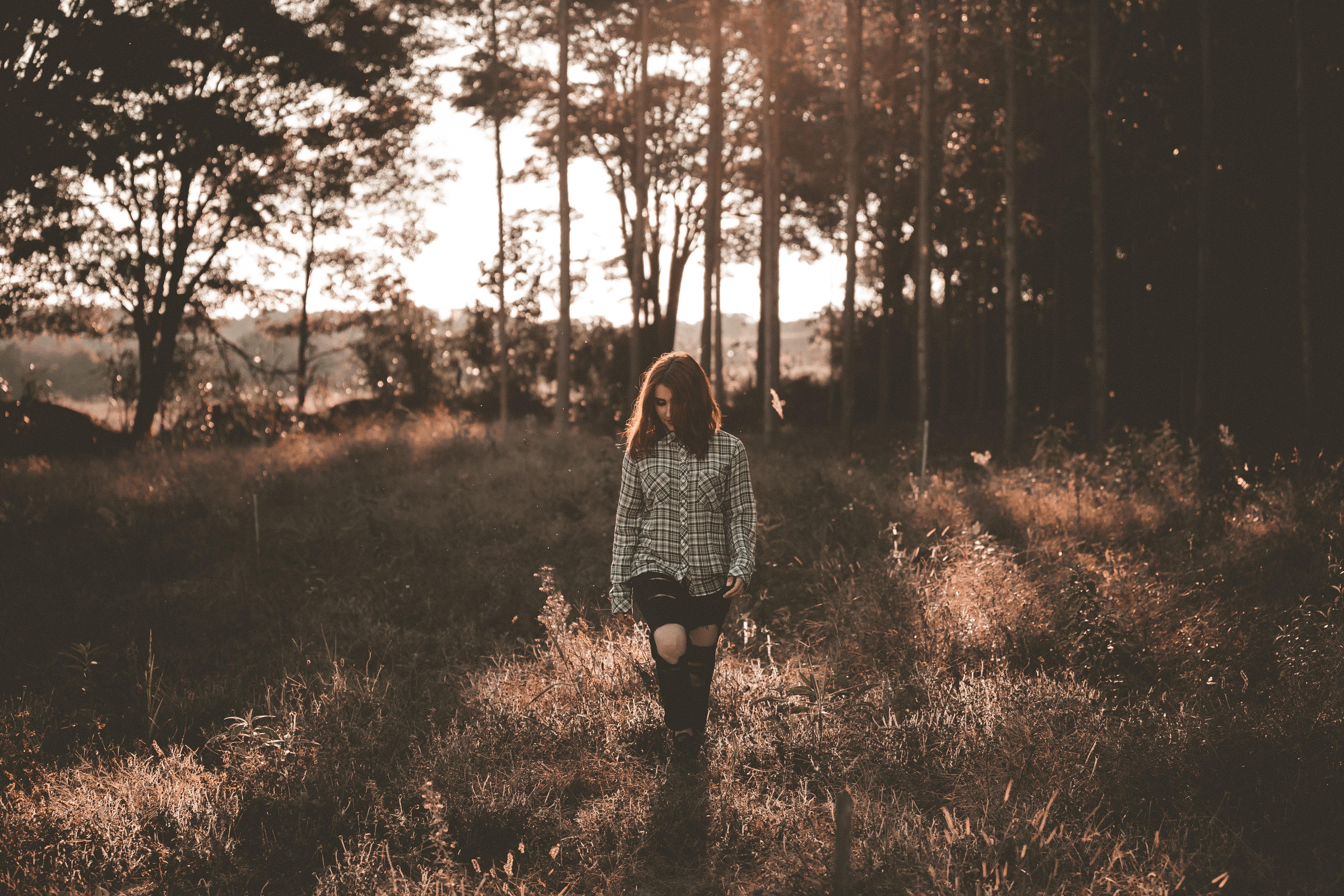 woman walking on brown grass field near trees