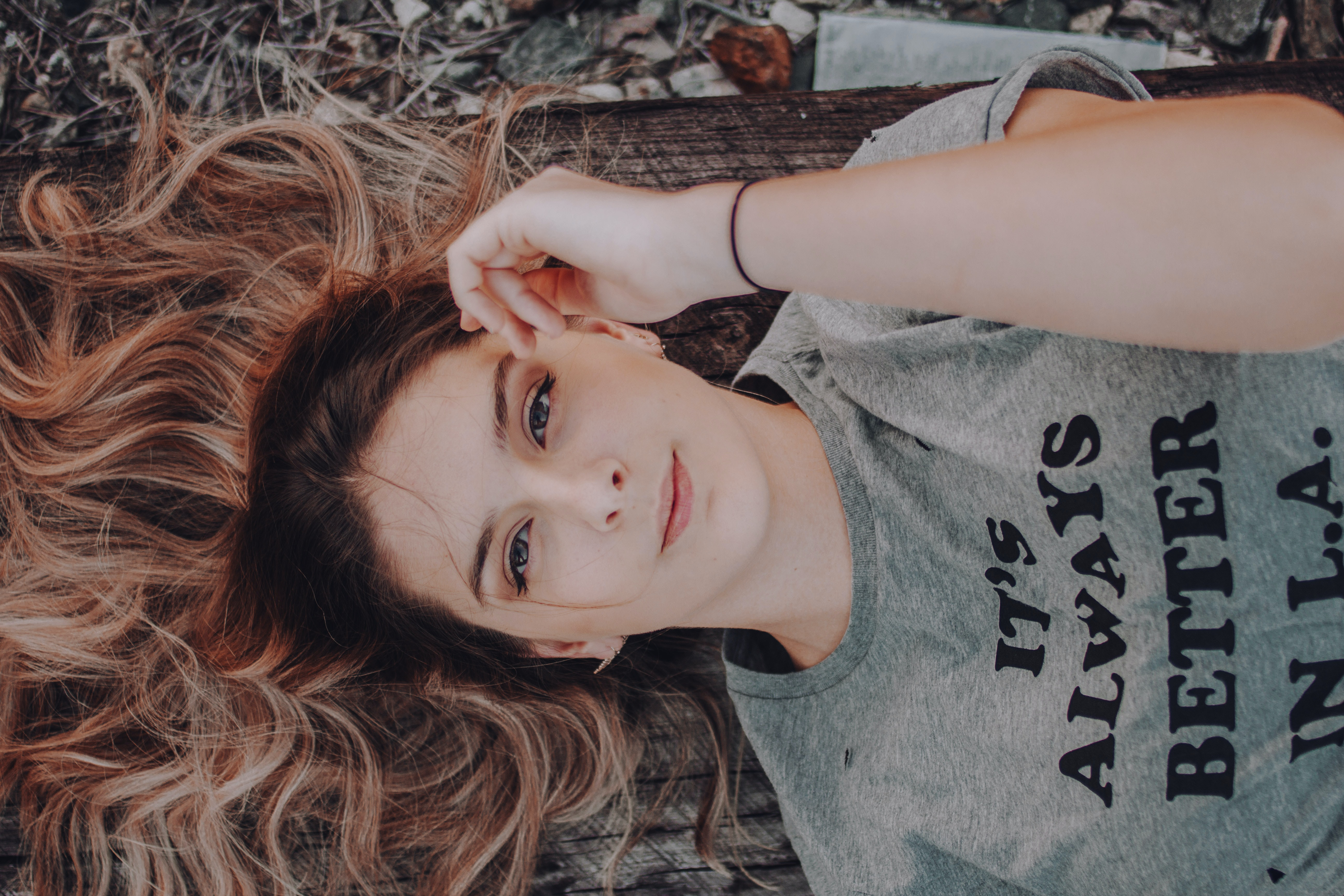 woman wearing gray t-shirt lying on ground