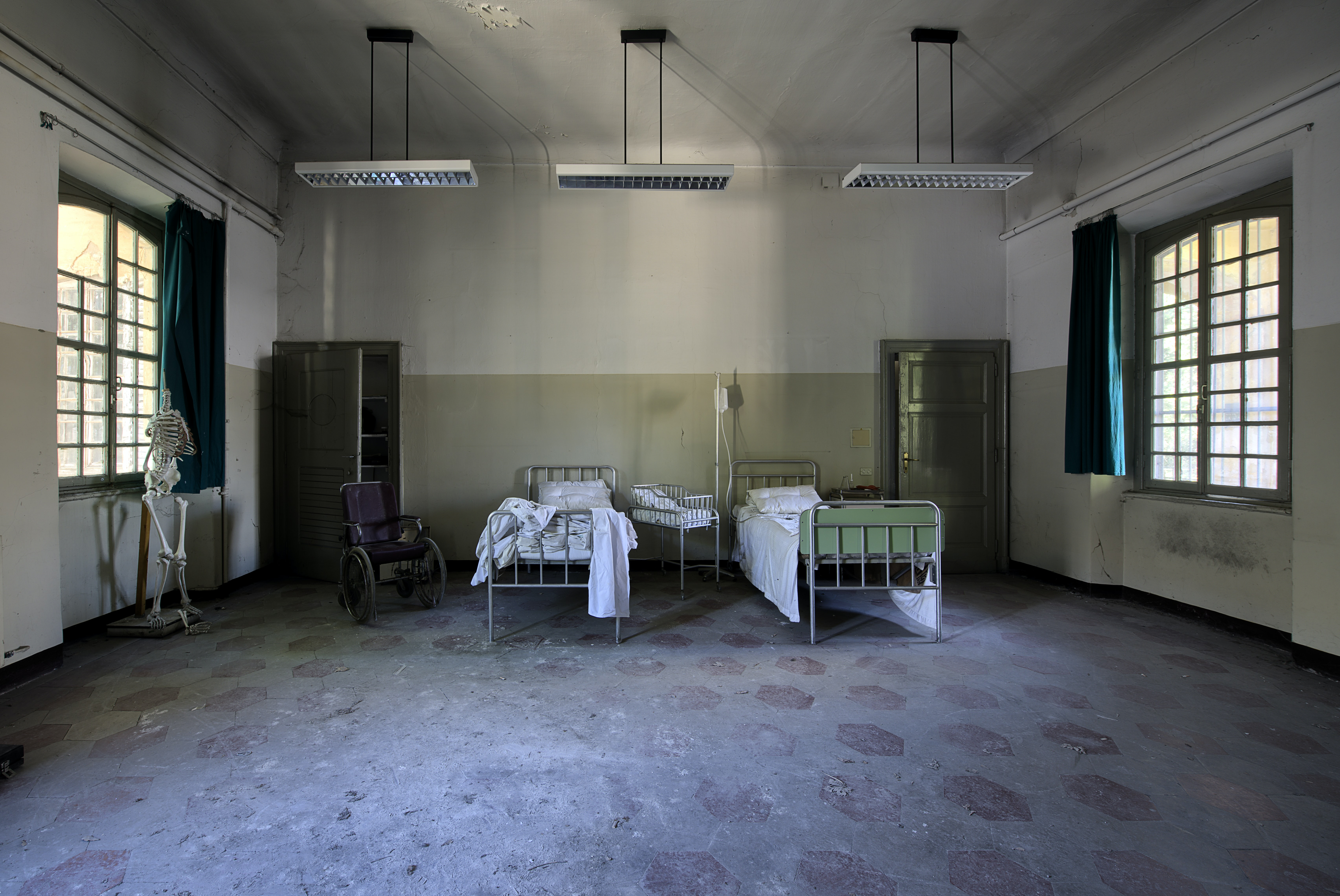 Two clinic beds in the middle of a ward room with windows on opposite walls