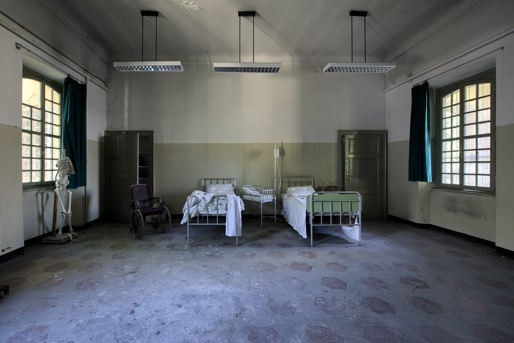 two hospital beds in spacious room under pendant lamps