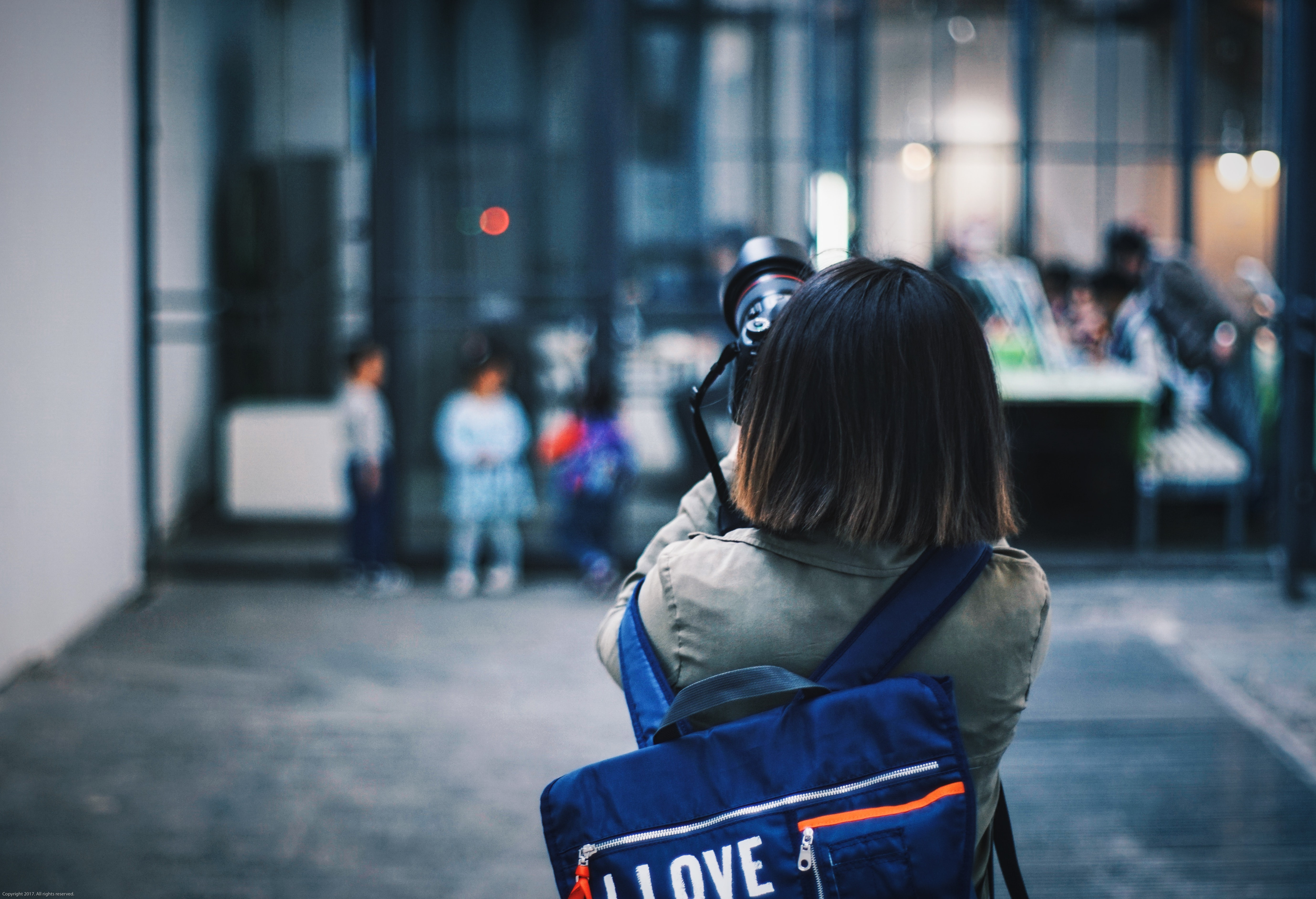 Young girl taking photograph with I love bag with people in background, Beijing 798 Art District