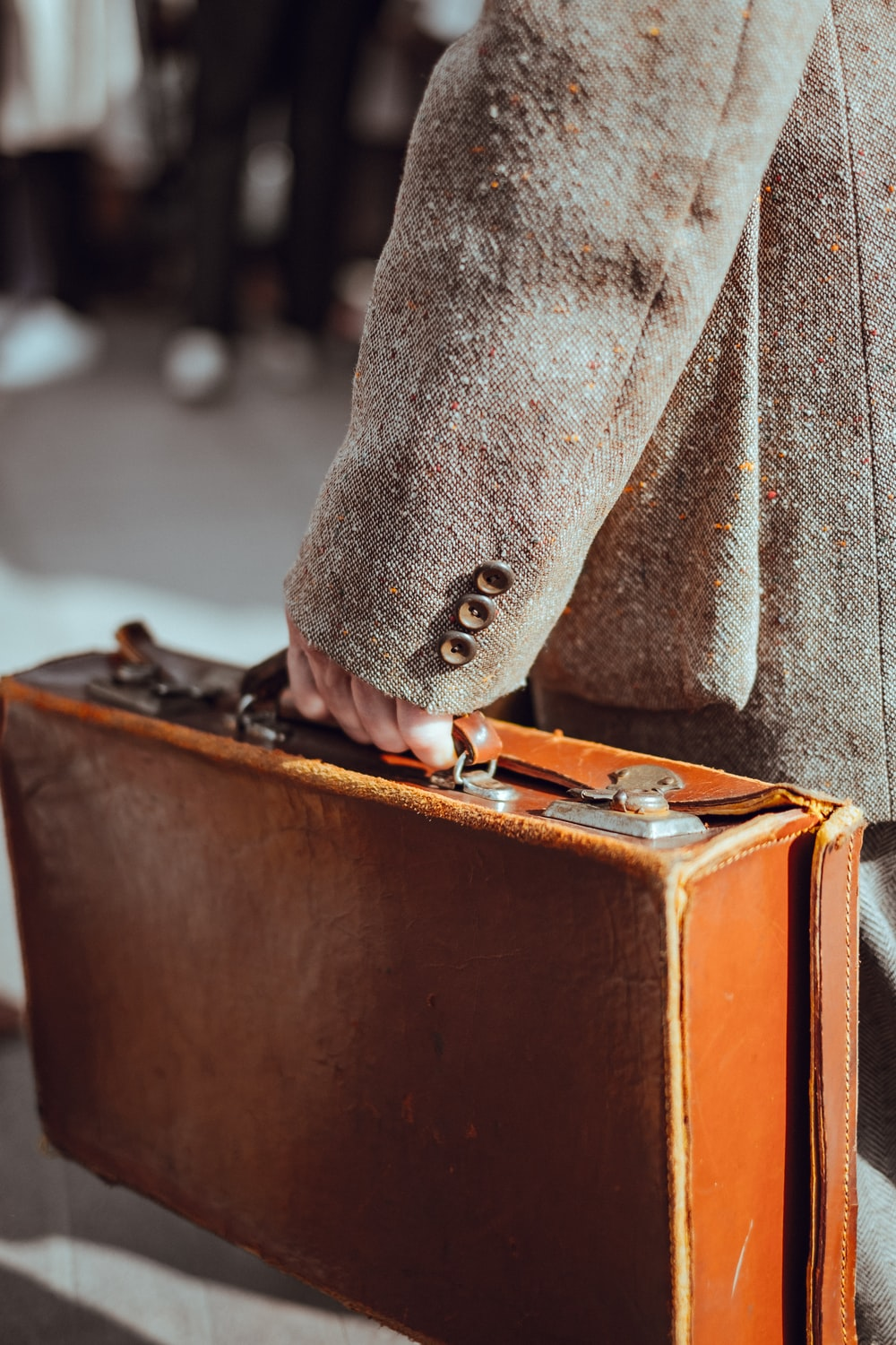 person wearing coat carrying suitcase