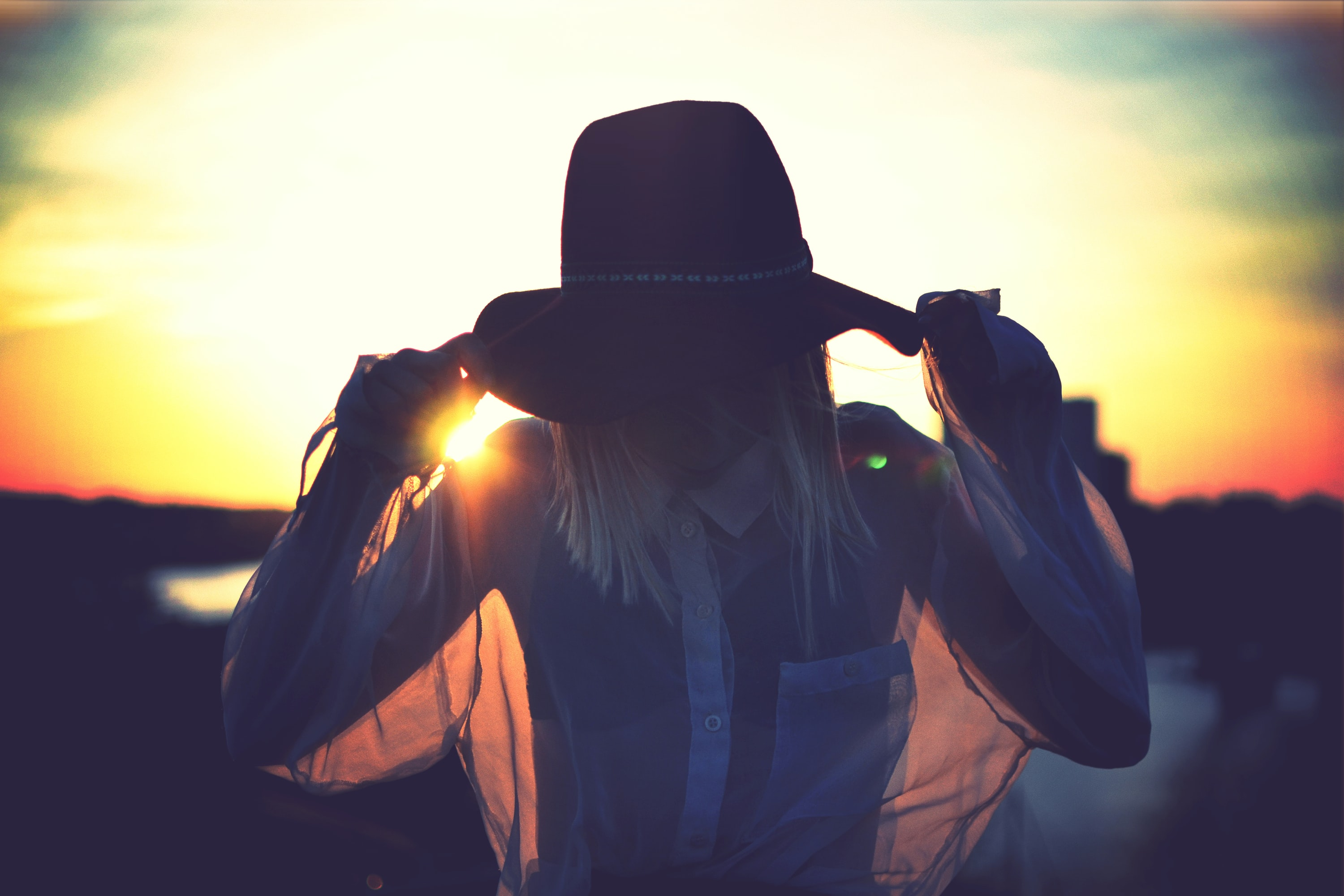 Woman in silhouette in a sheer shirt and hat before the setting sun in Långholmen