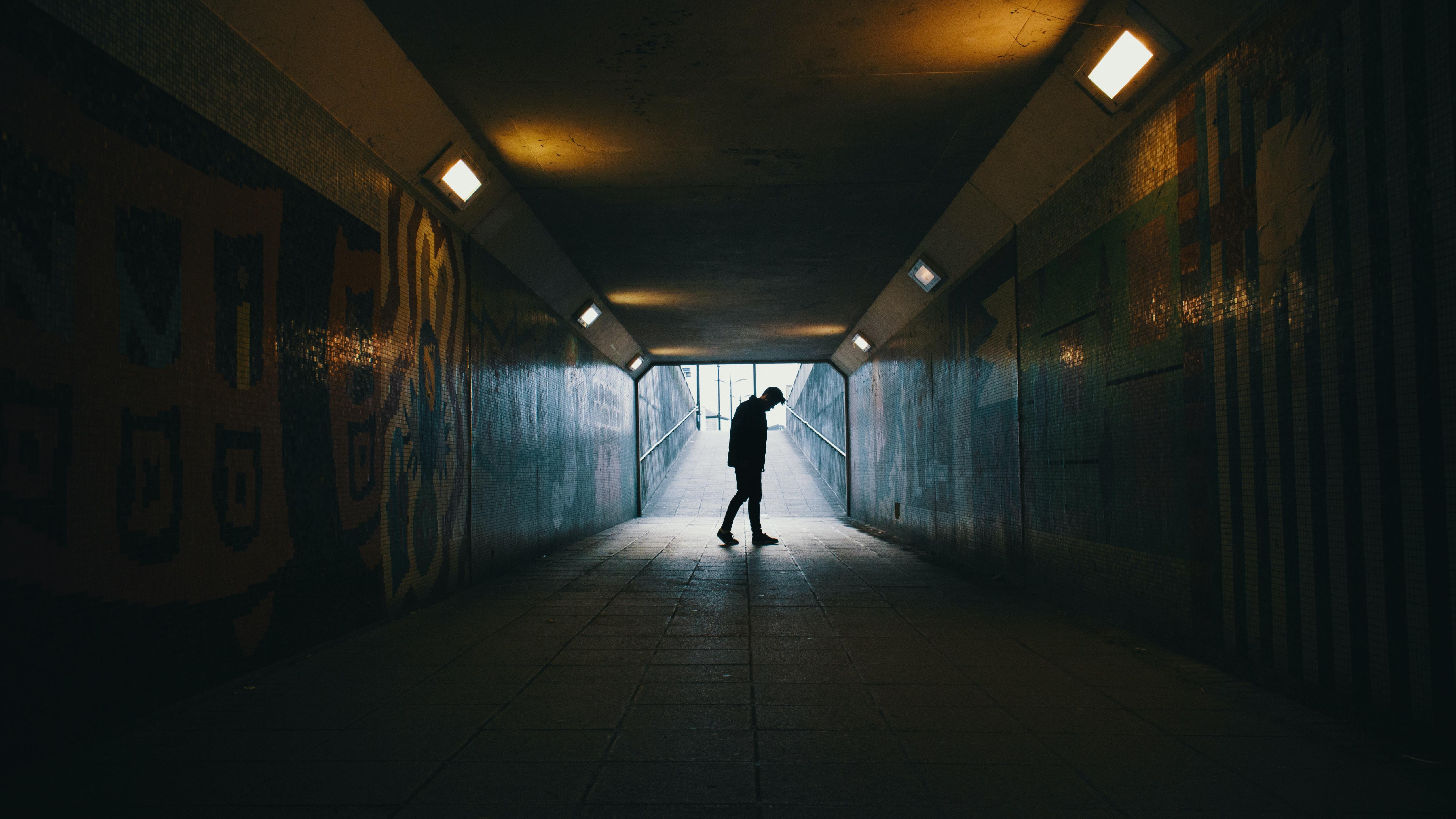 Silhouette of sad person walking through an urban tunnel
