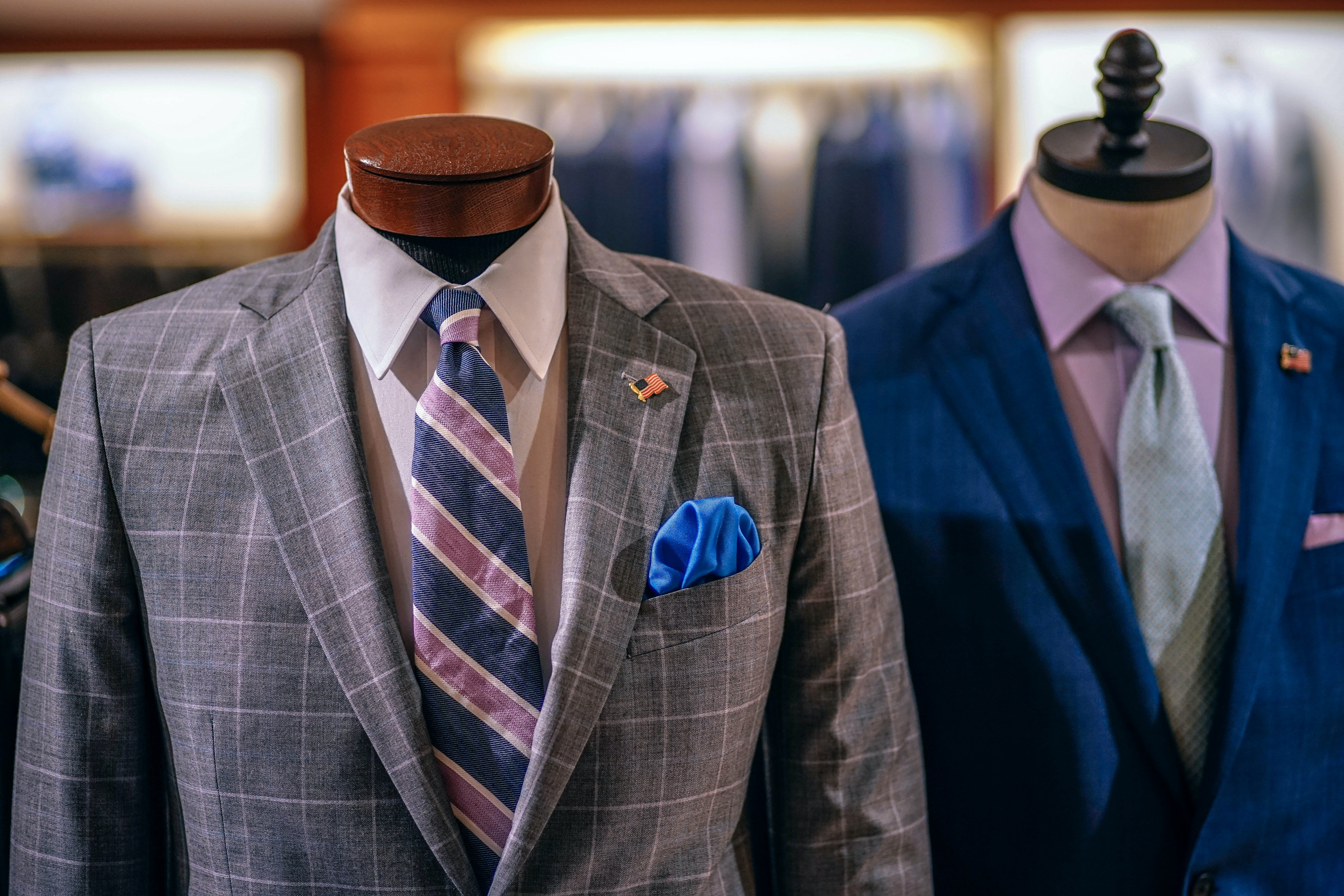 Suits on display at a clothing store.