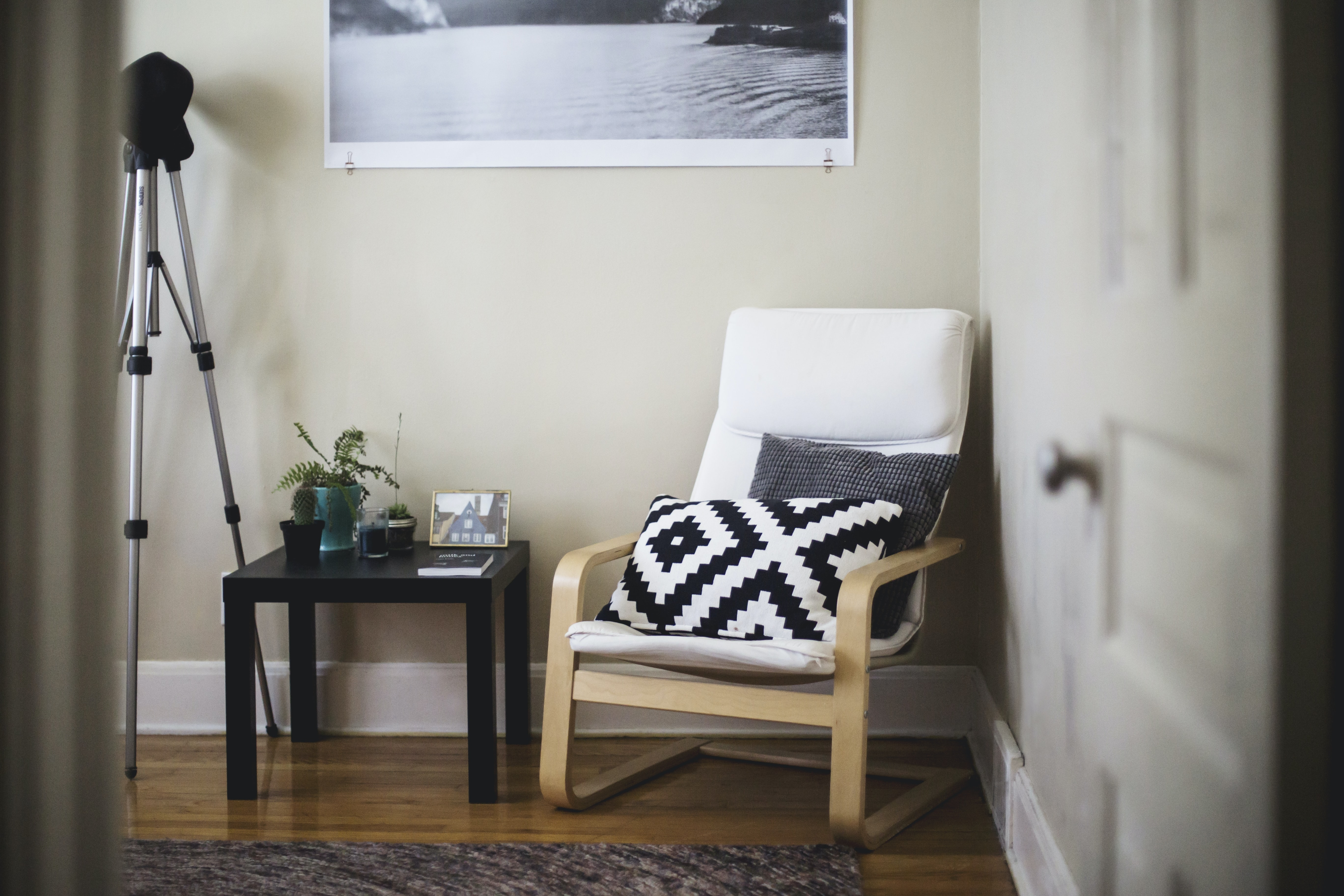 A chair with two pillows next to a coffee table in the corner of a room