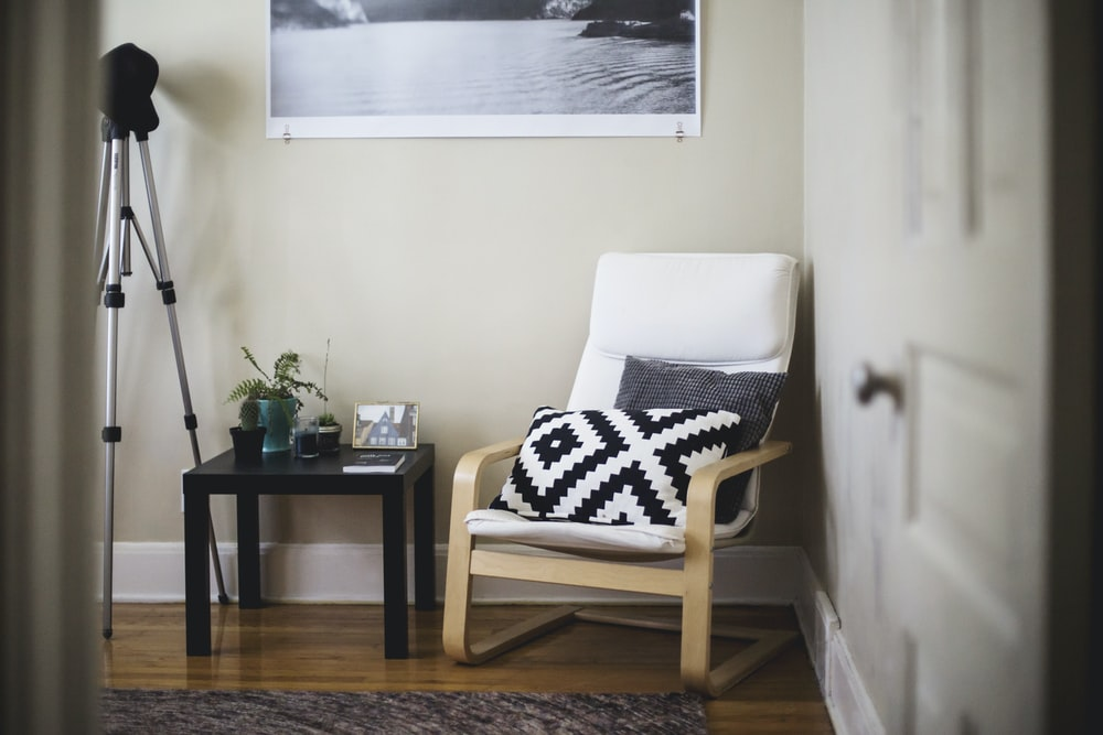 throw pillow on chair beside end table inside room