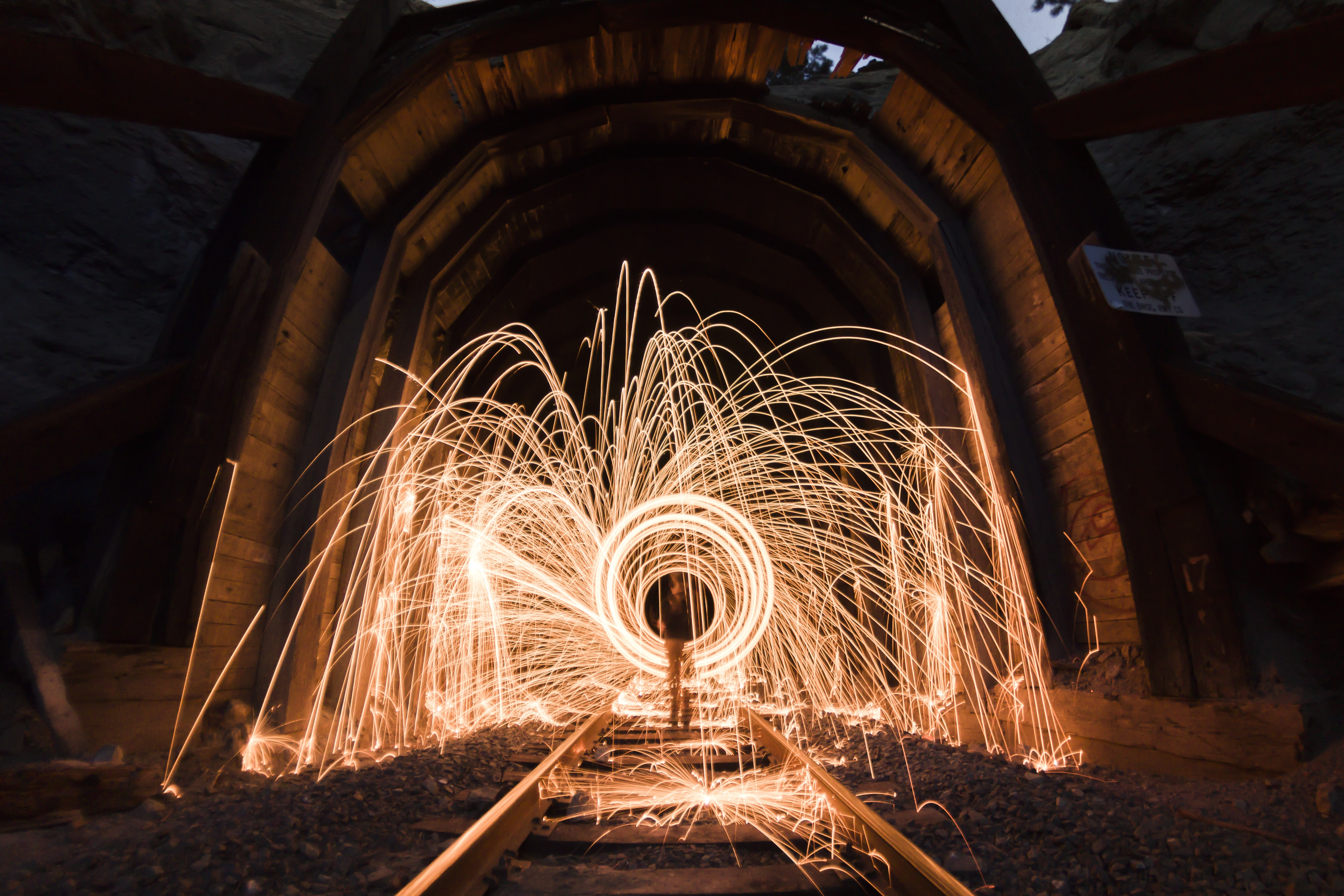 A long exposure shot of steel wool light trails in a tunnel after dark