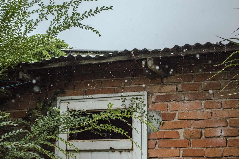 rain pouring on brick wall house