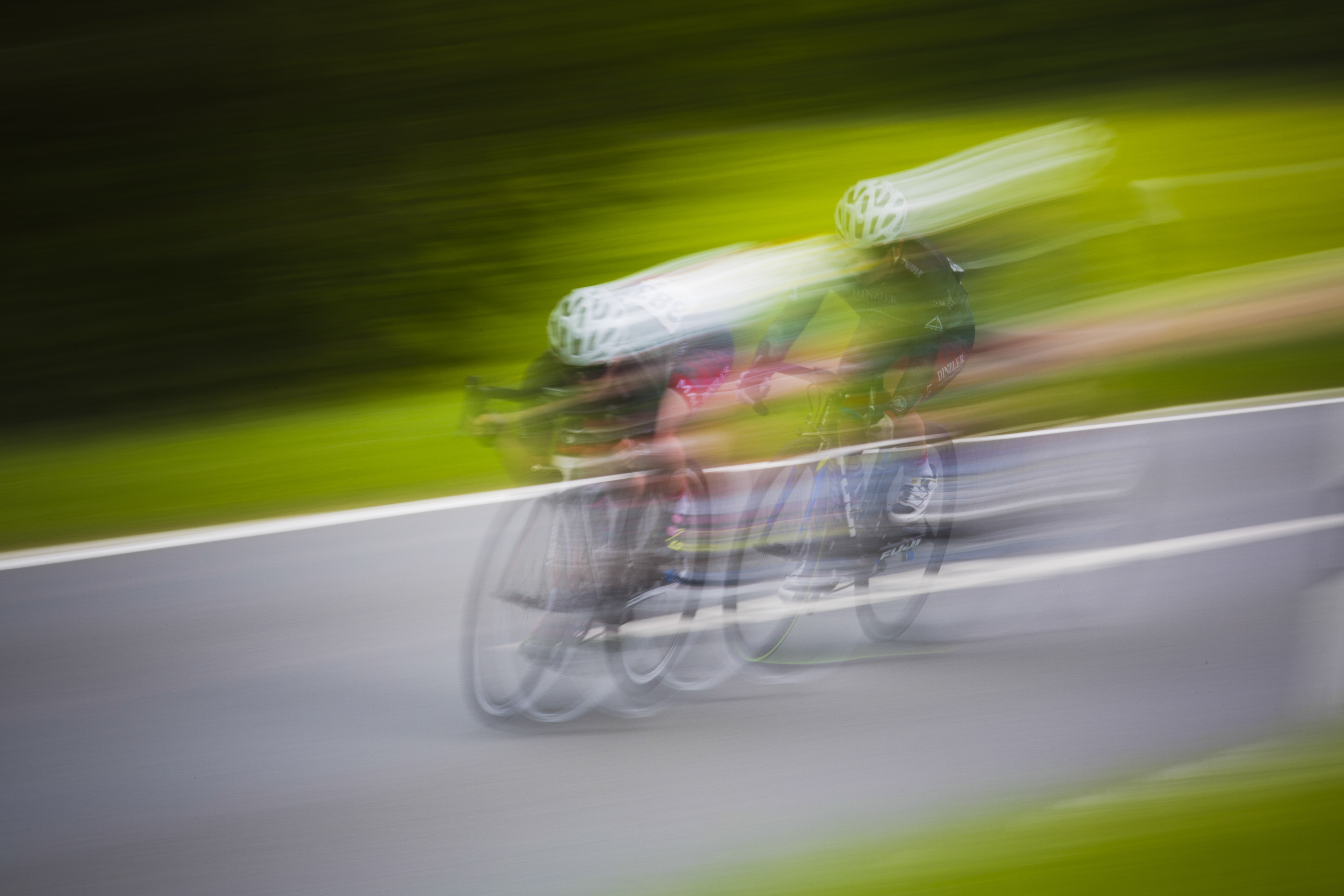 Long exposure of two cyclists in helmets racing on a road