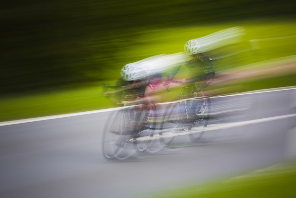 motion photography of two men riding mountain bikes