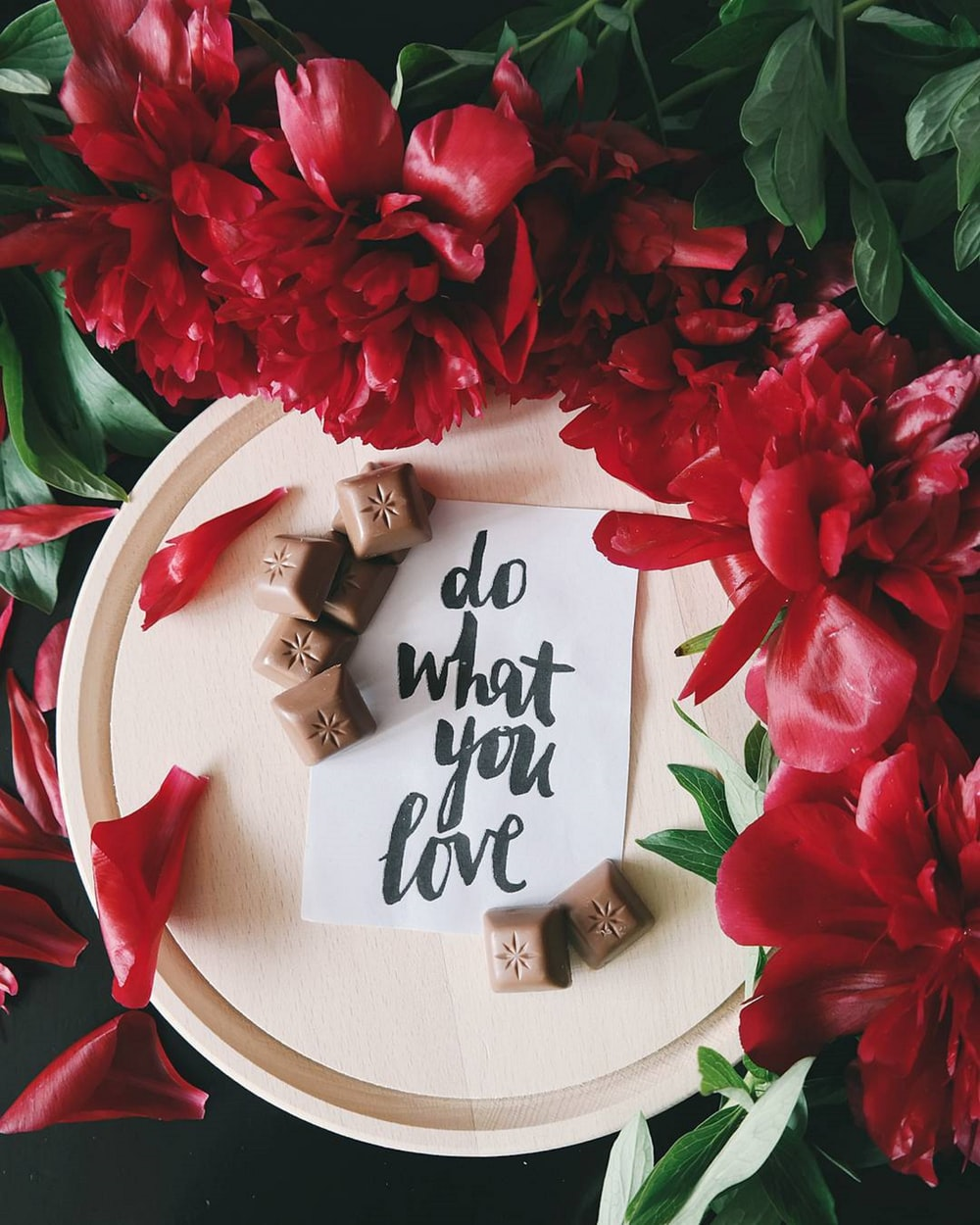 "A note on a piece of paper on top of a plate next to red flowers that reads ""Do what you love."""