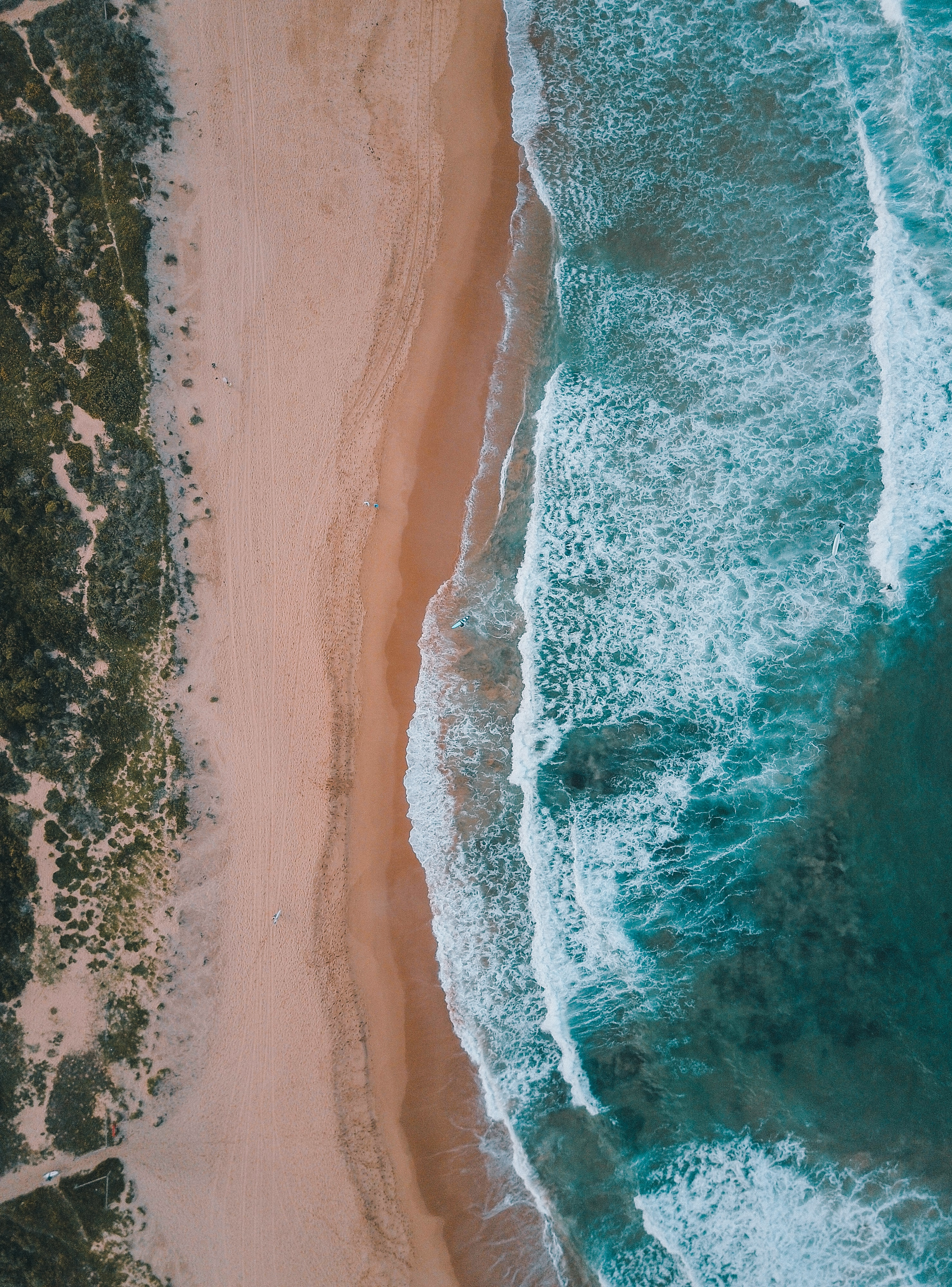 Drone aerial view of the ocean washing on the Mona Vale Beach