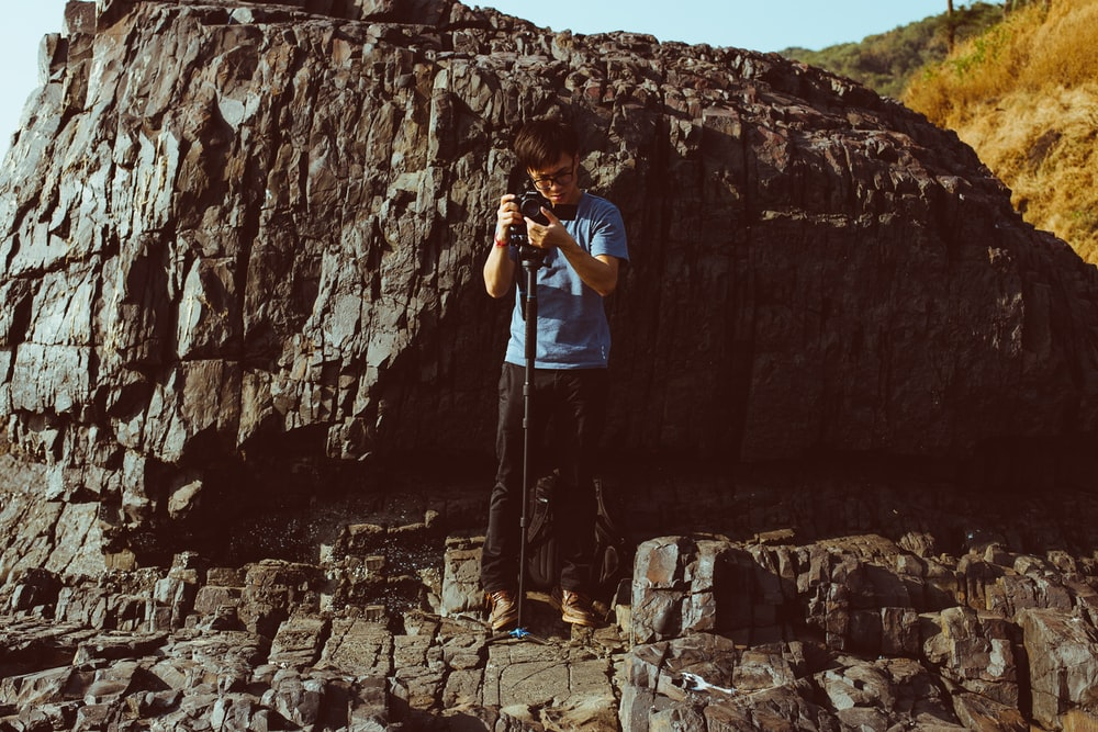 man holding camera while standing on cliff during daytime