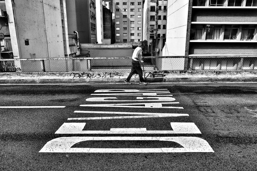 gray scale photography of person walking beside pave road