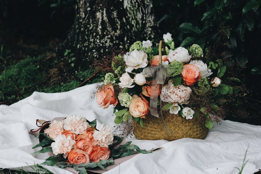 Roses and peonies in a basket and a bouquet on white cloth on the ground