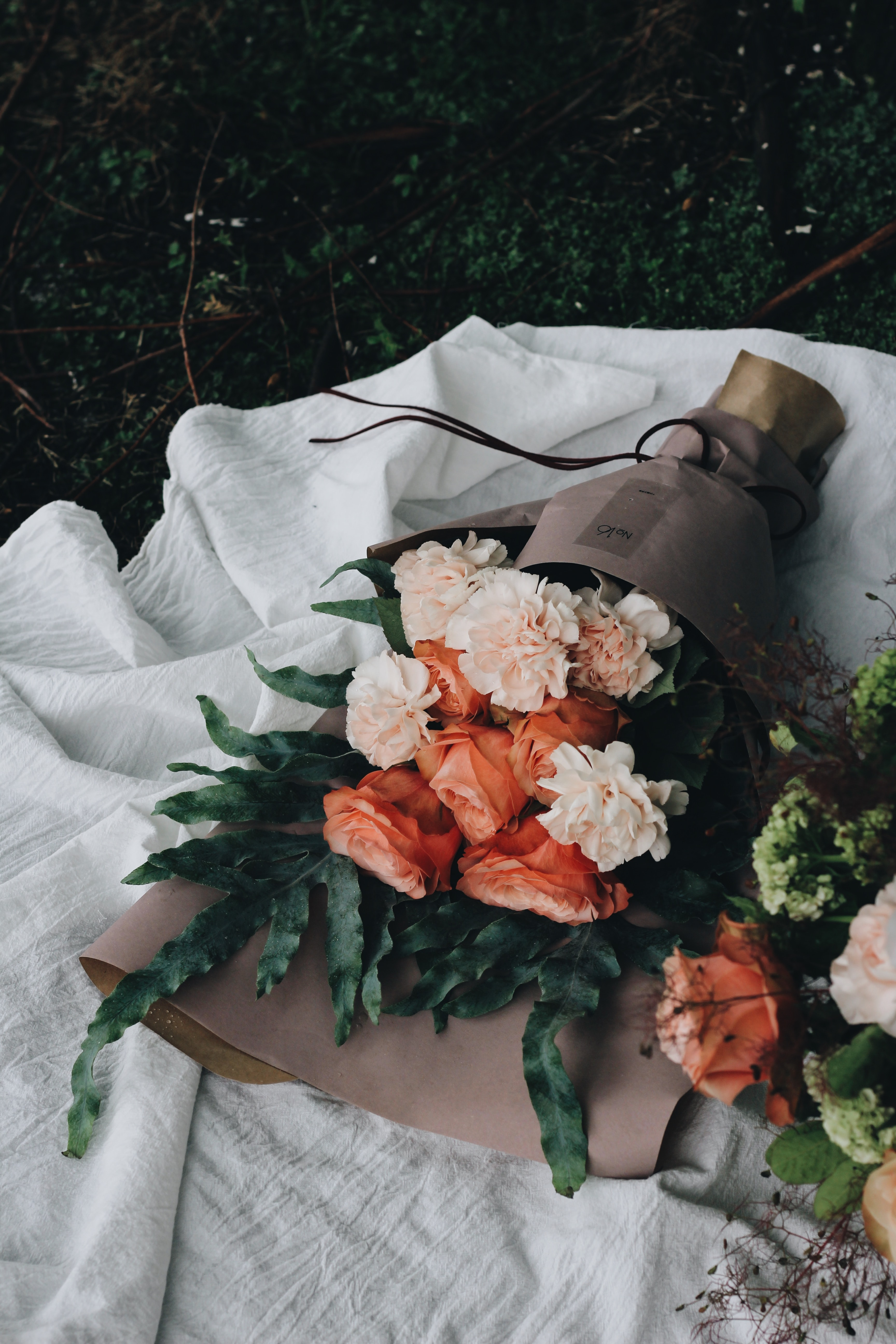 Large bouquets of pink carnations wrapped in paper and laid down on the ground